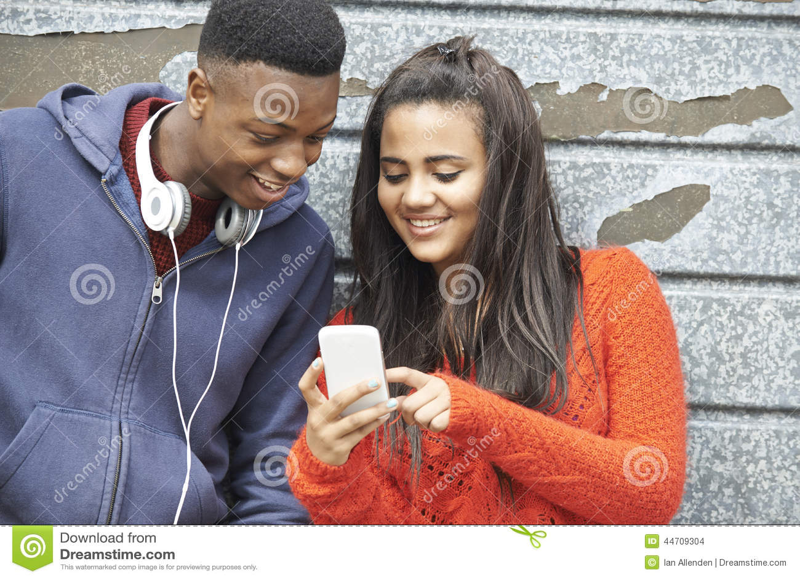Couples adolescents partageant le message textuel au téléphone portable