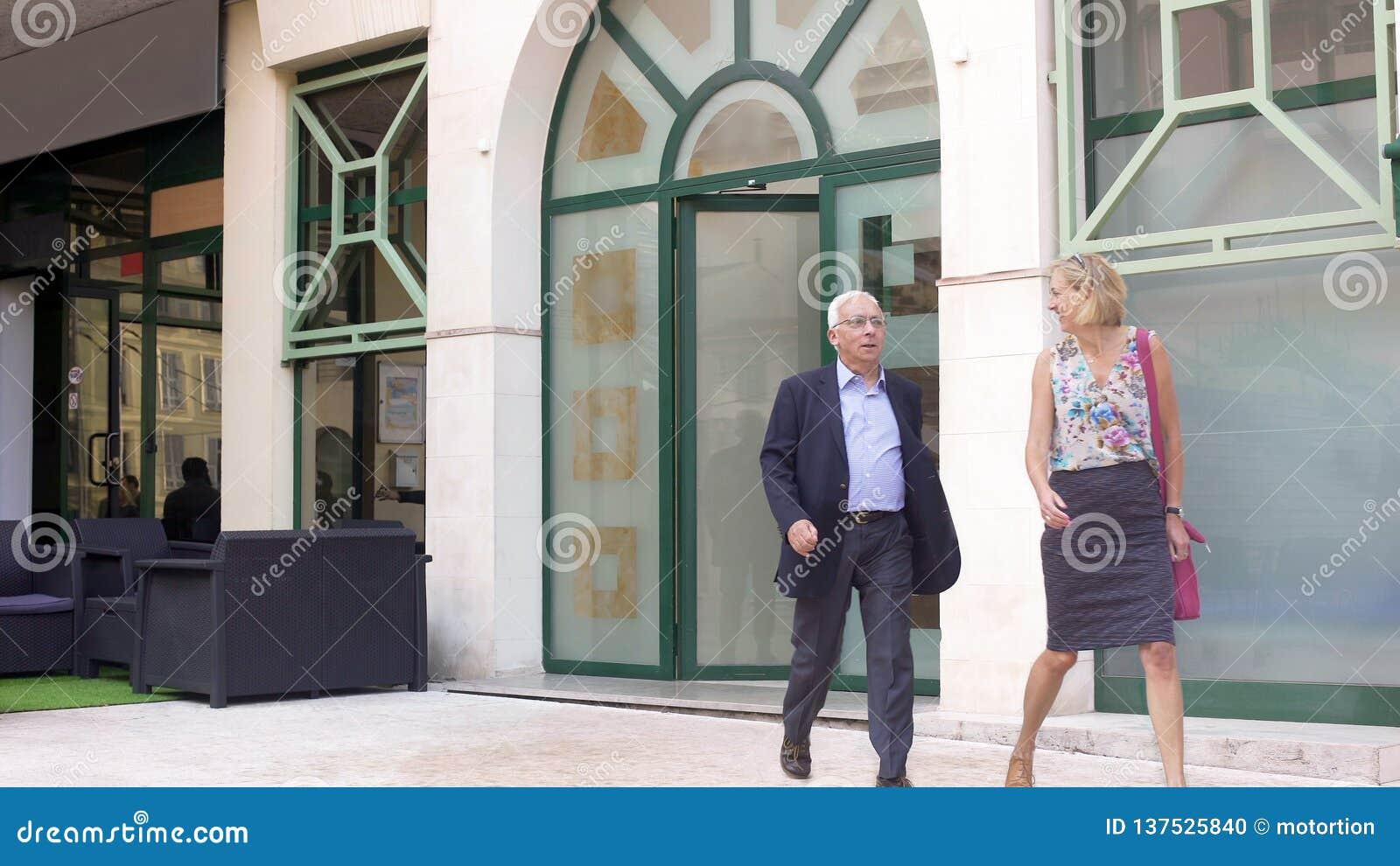 Couples adultes heureux quittant le restaurant, satisfait du service, déjeuner d affaires
