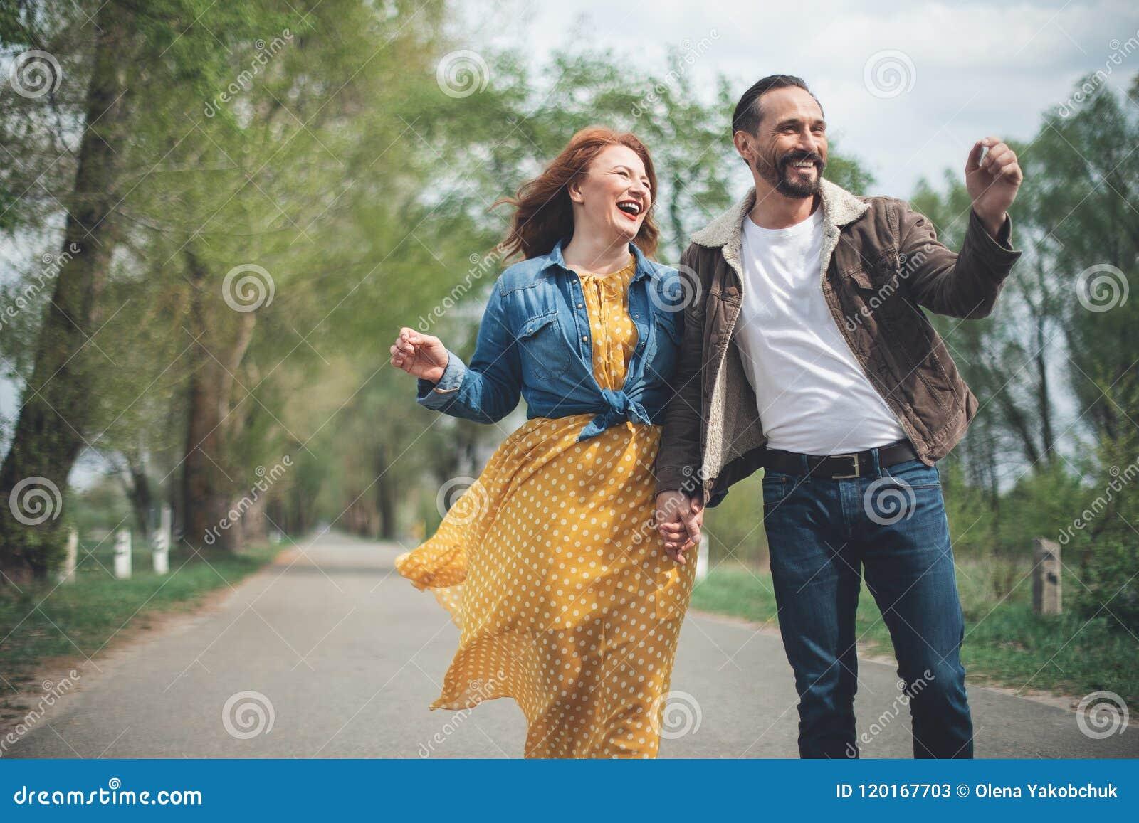 Couples affectueux mûrs joyeux marchant le long de l allée de parc