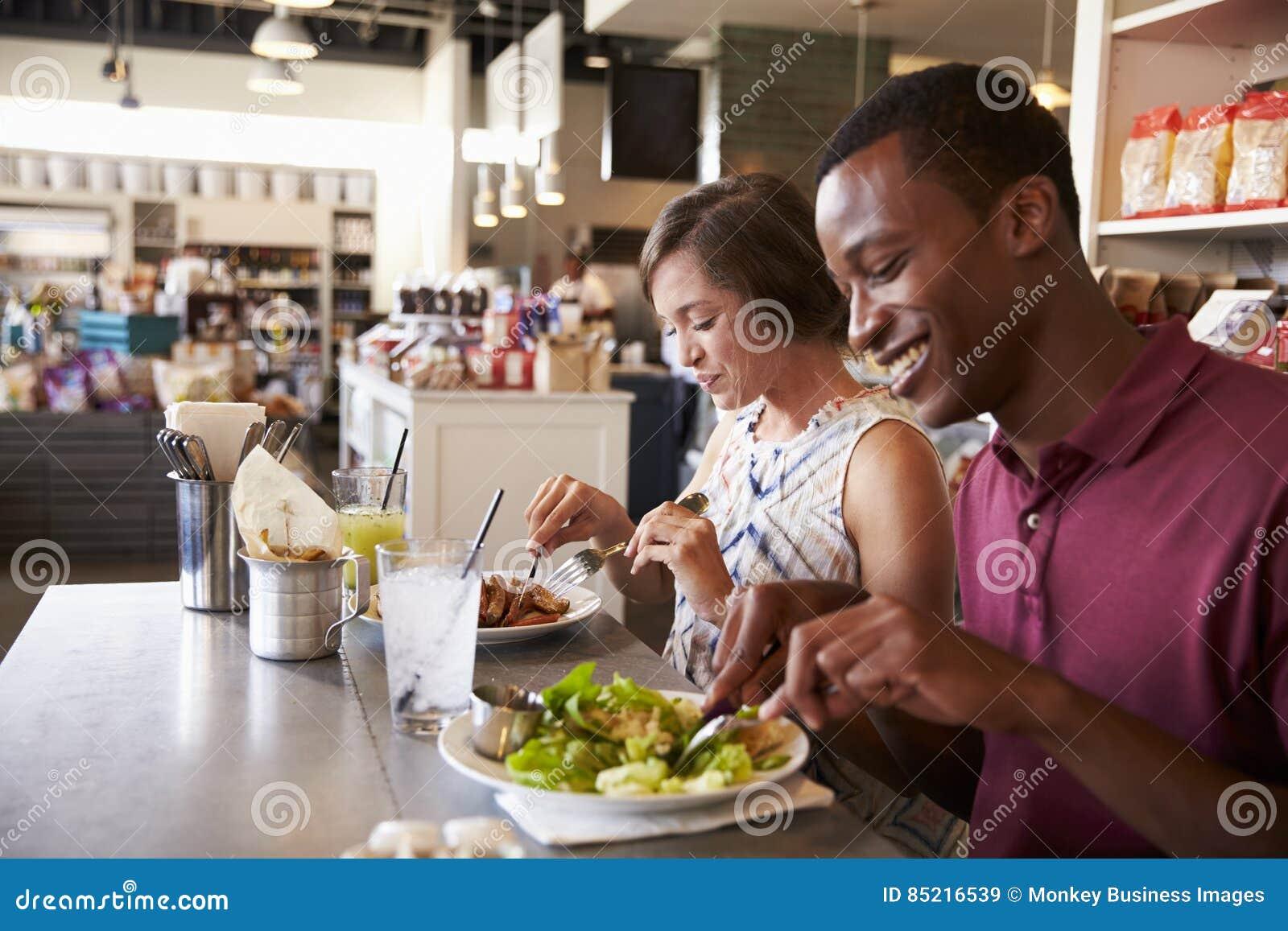 Couples appréciant la date de déjeuner dans le restaurant d épicerie fine