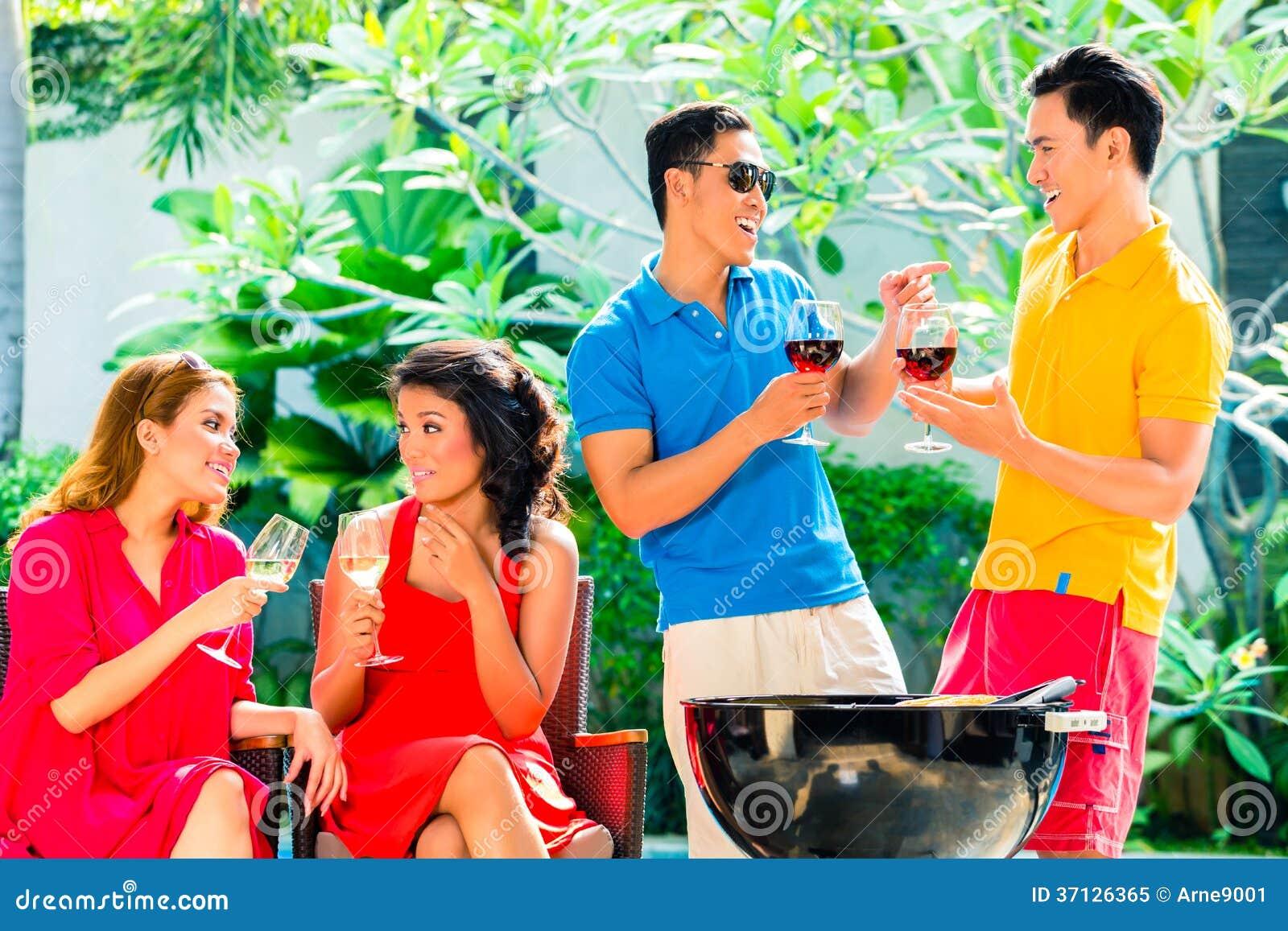 Couples asiatiques ayant le barbecue et buvant du vin