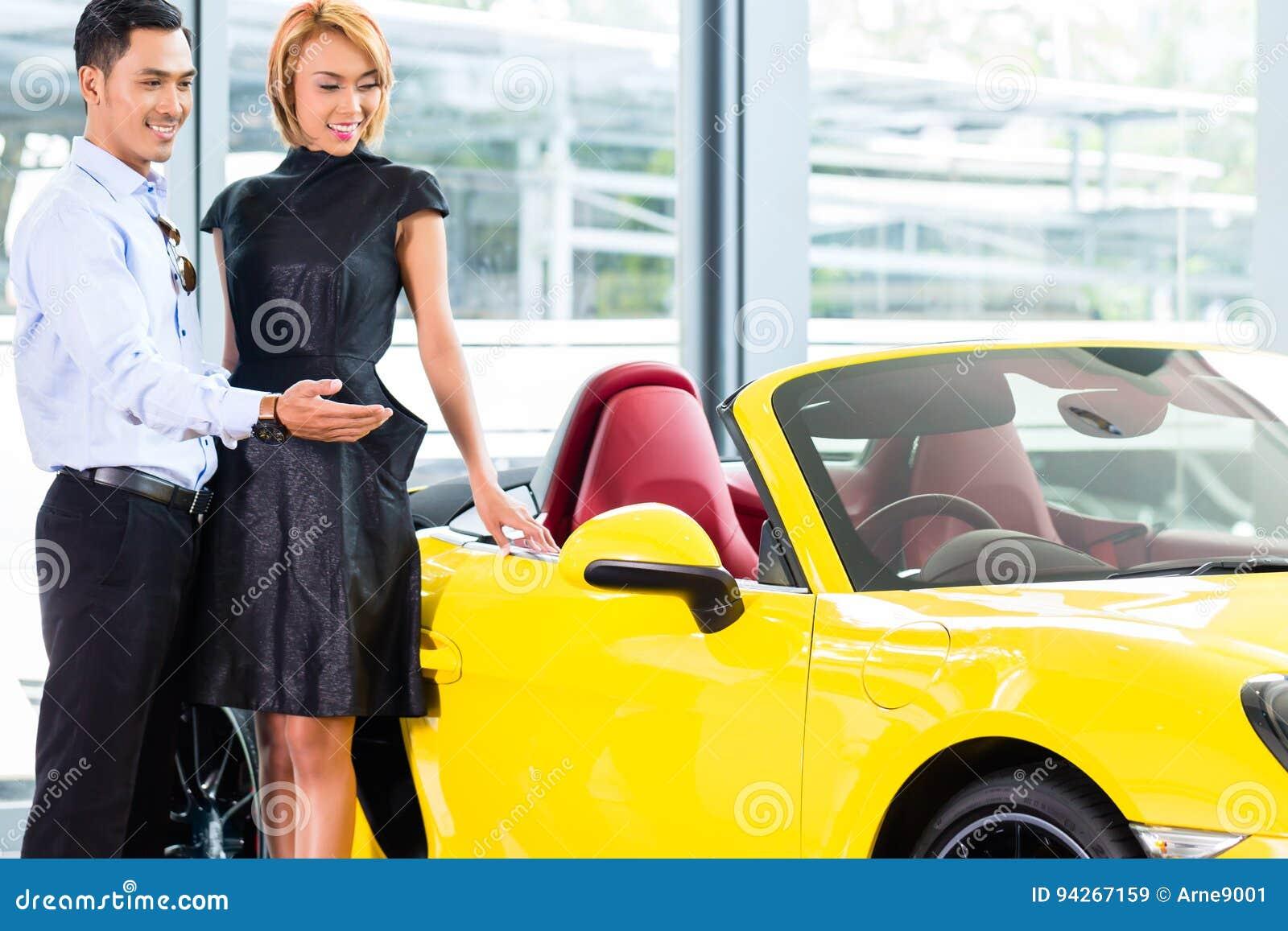 Couples asiatiques choisissant la voiture de roadster au concessionnaire