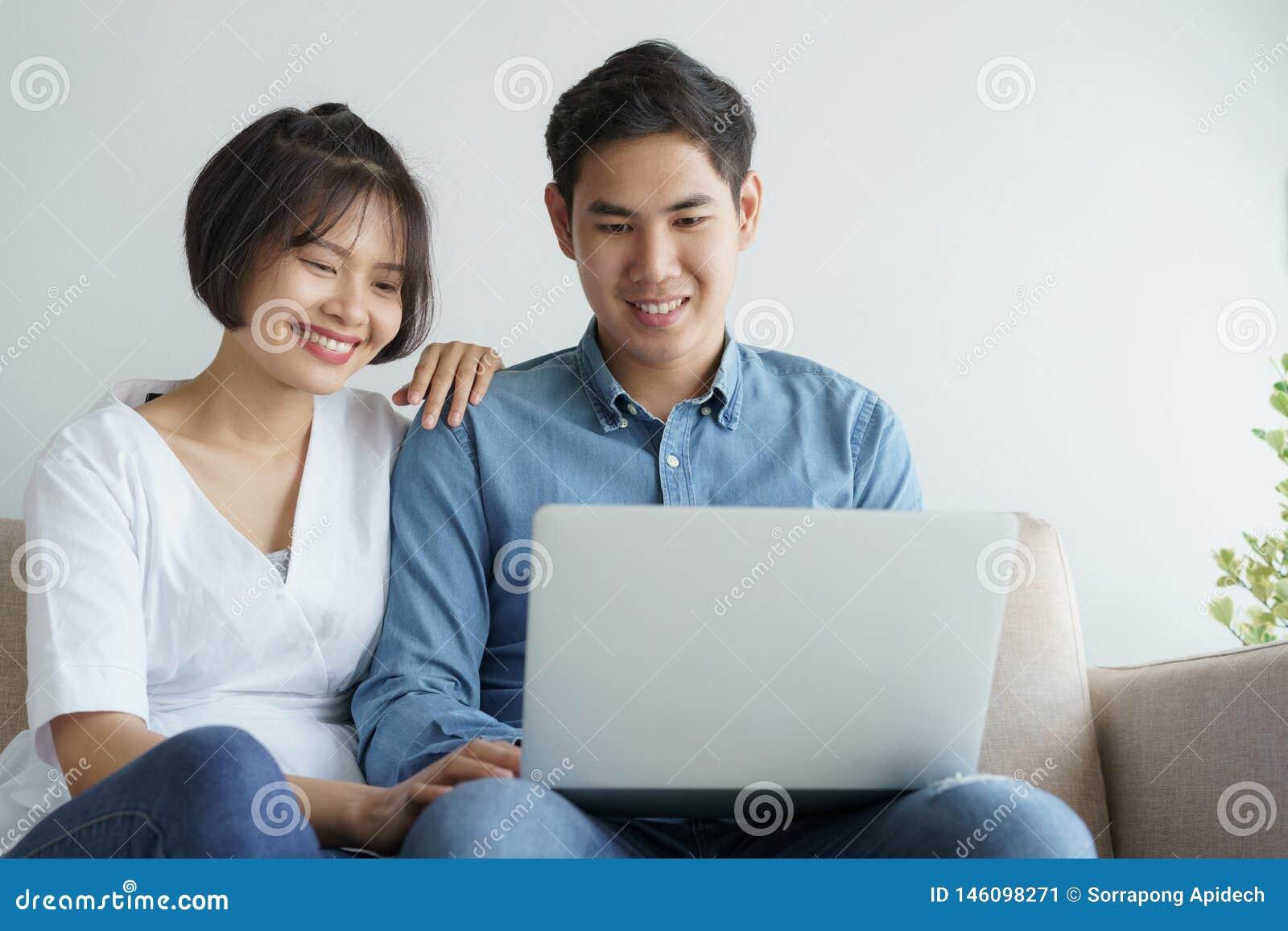 Couples asiatiques d amour se reposant sur le sofa et à l aide de l ordinateur portable ils souriant heureusement à la maison