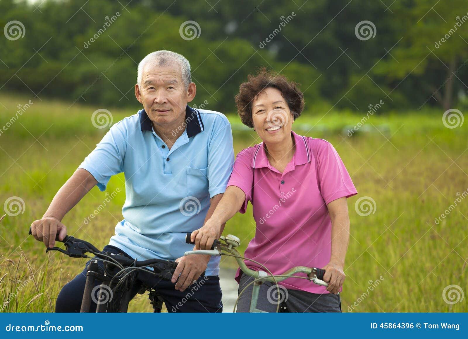 Couples asiatiques heureux d aînés faisant du vélo en parc