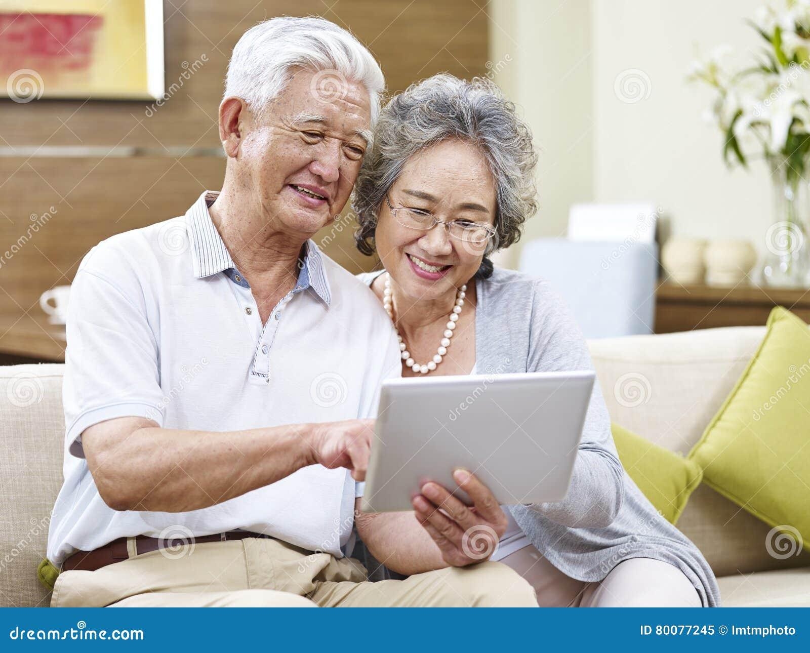 Couples asiatiques supérieurs utilisant une tablette ensemble