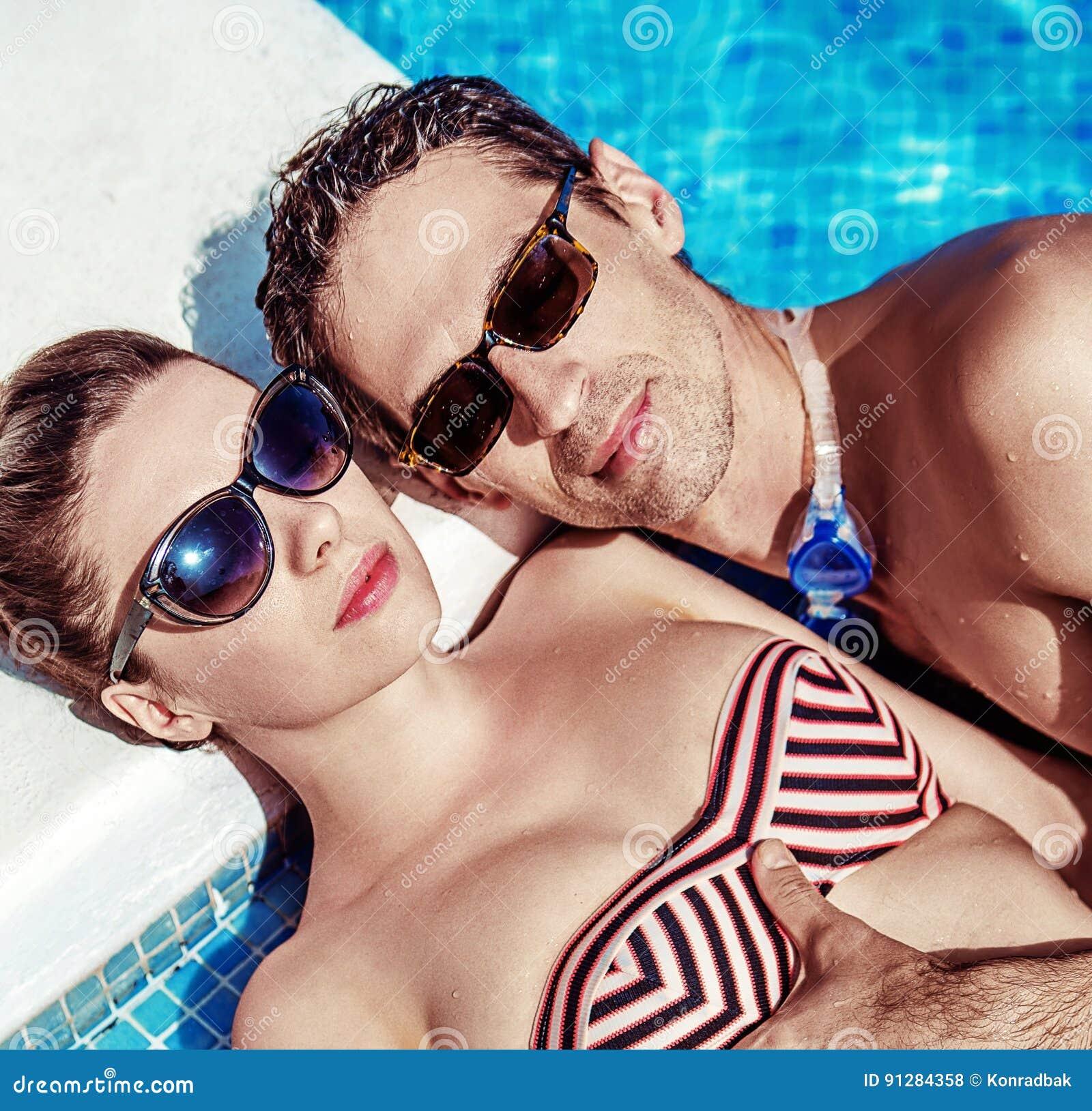 Couples attrayants détendant par la piscine