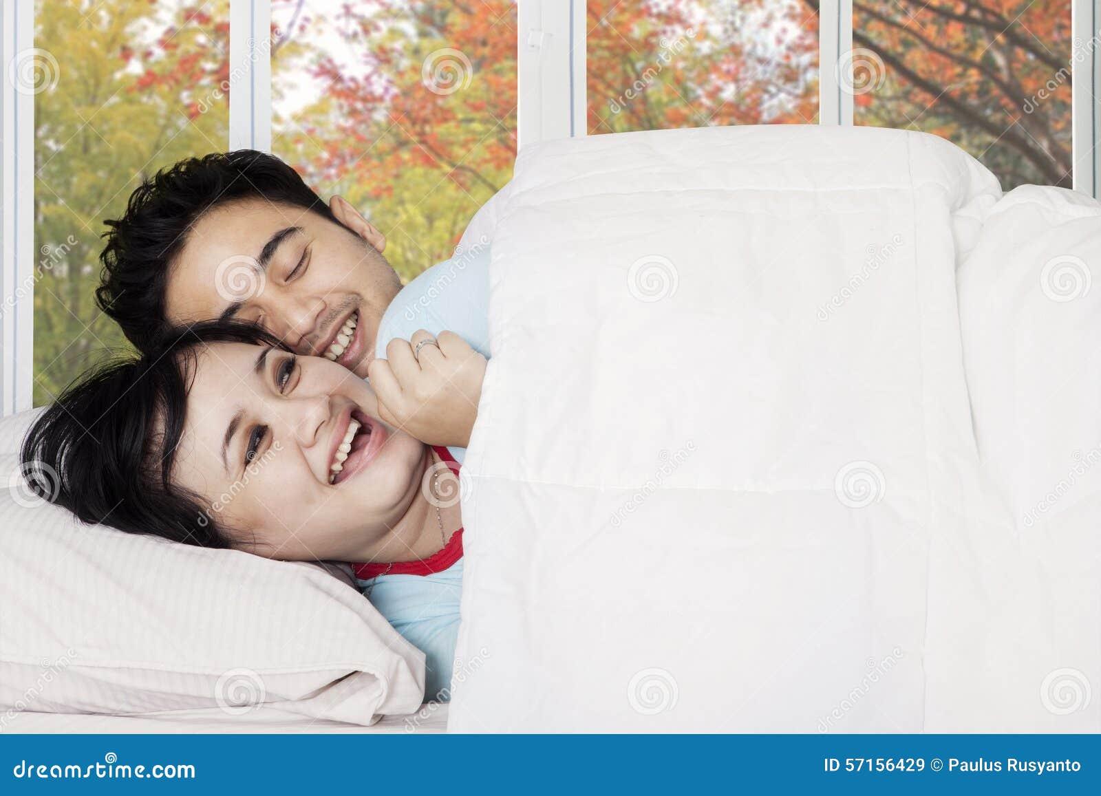 couples attrayants plaisantant sur le lit photo stock image 57156429. Black Bedroom Furniture Sets. Home Design Ideas