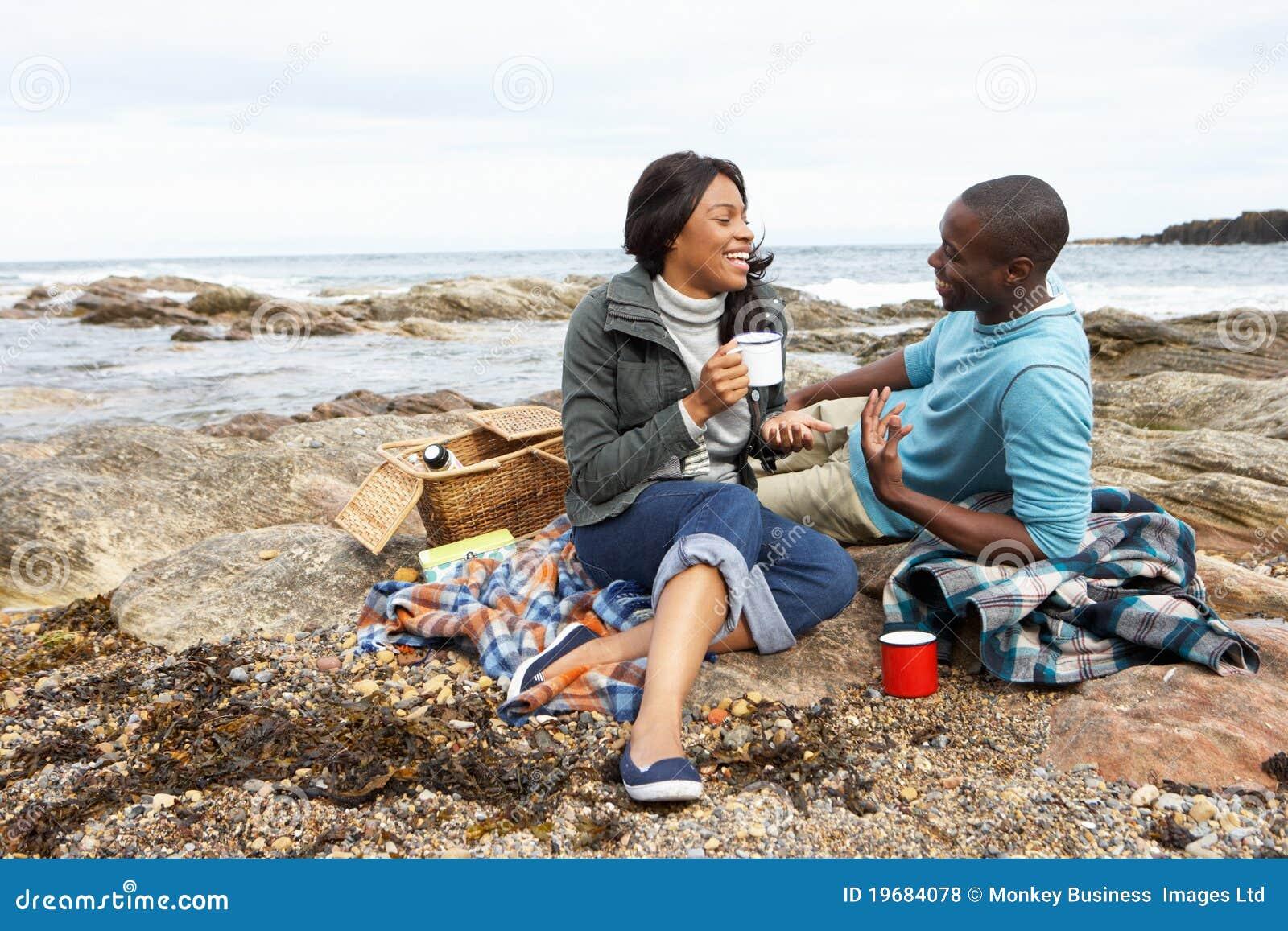 couples ayant le pique nique sur la plage photo stock. Black Bedroom Furniture Sets. Home Design Ideas