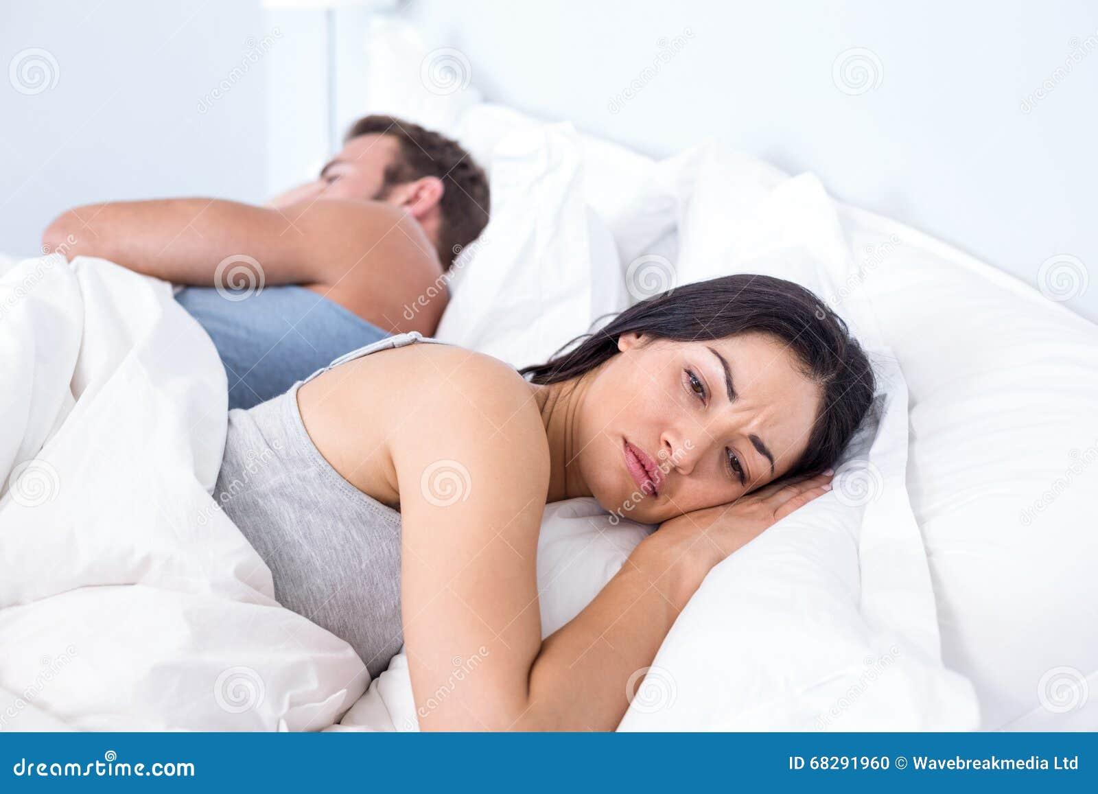 Couples bouleversés se trouvant sur le lit