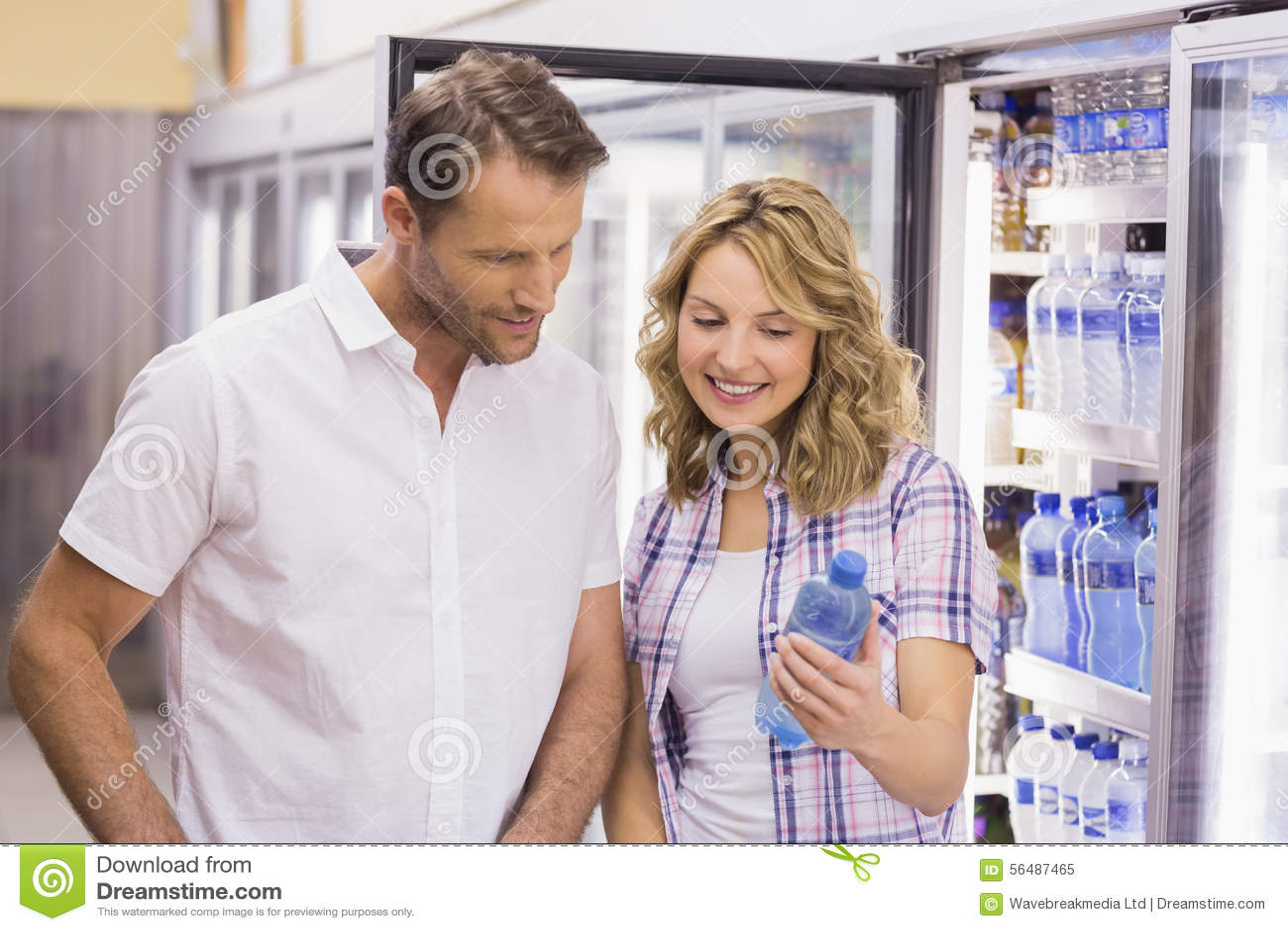 Couples cacual de sourire regardant la bouteille d eau