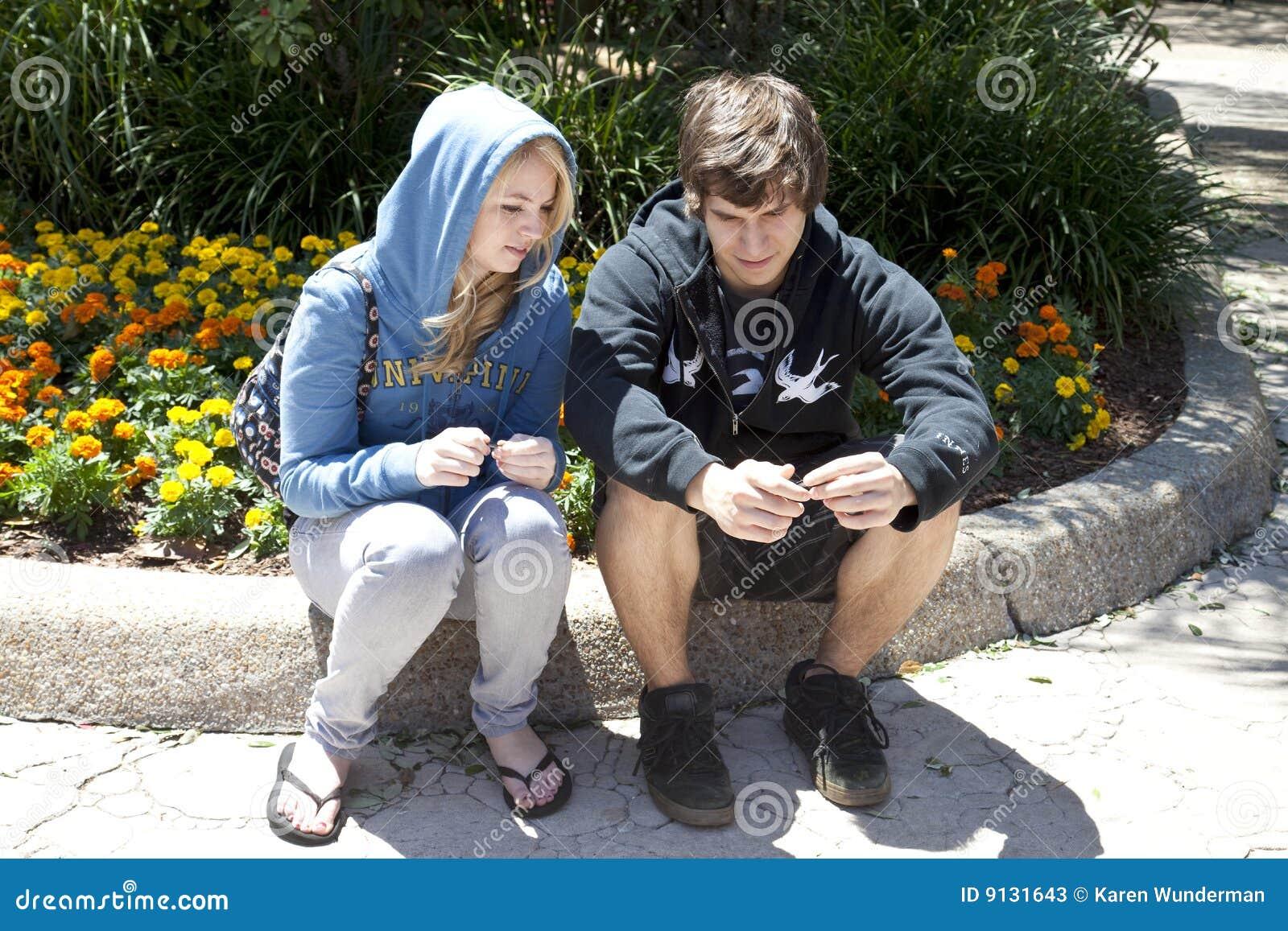 Couples d adolescent se reposant sur la bordure de trottoir