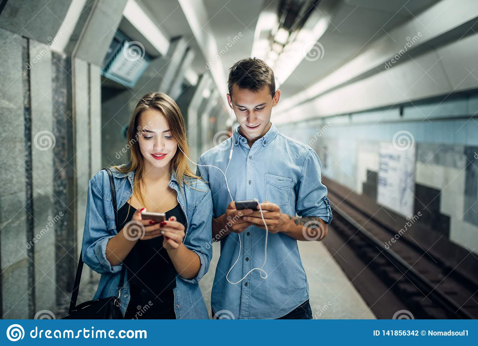 Couples d intoxiqué de téléphone utilisant l instrument dans le souterrain