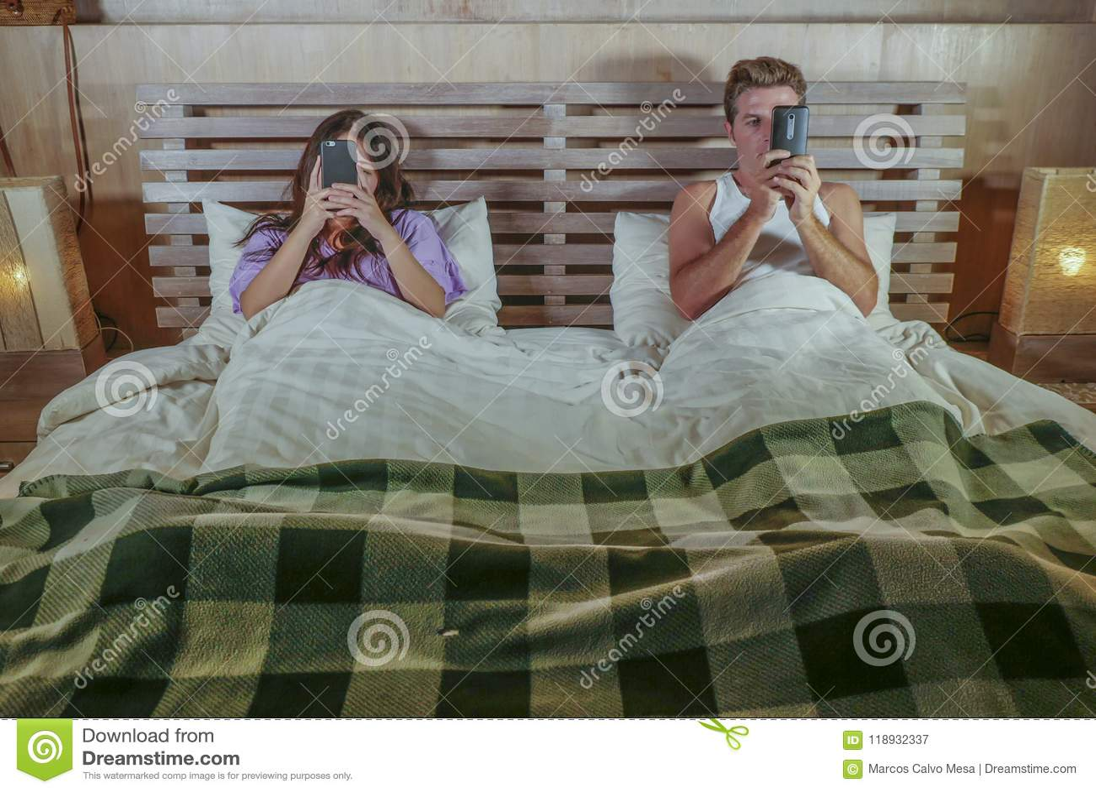 Couples d intoxiqué d Internet sur le lit s ignorant utilisant le media social APP au téléphone portable flirtant et sur la ligne