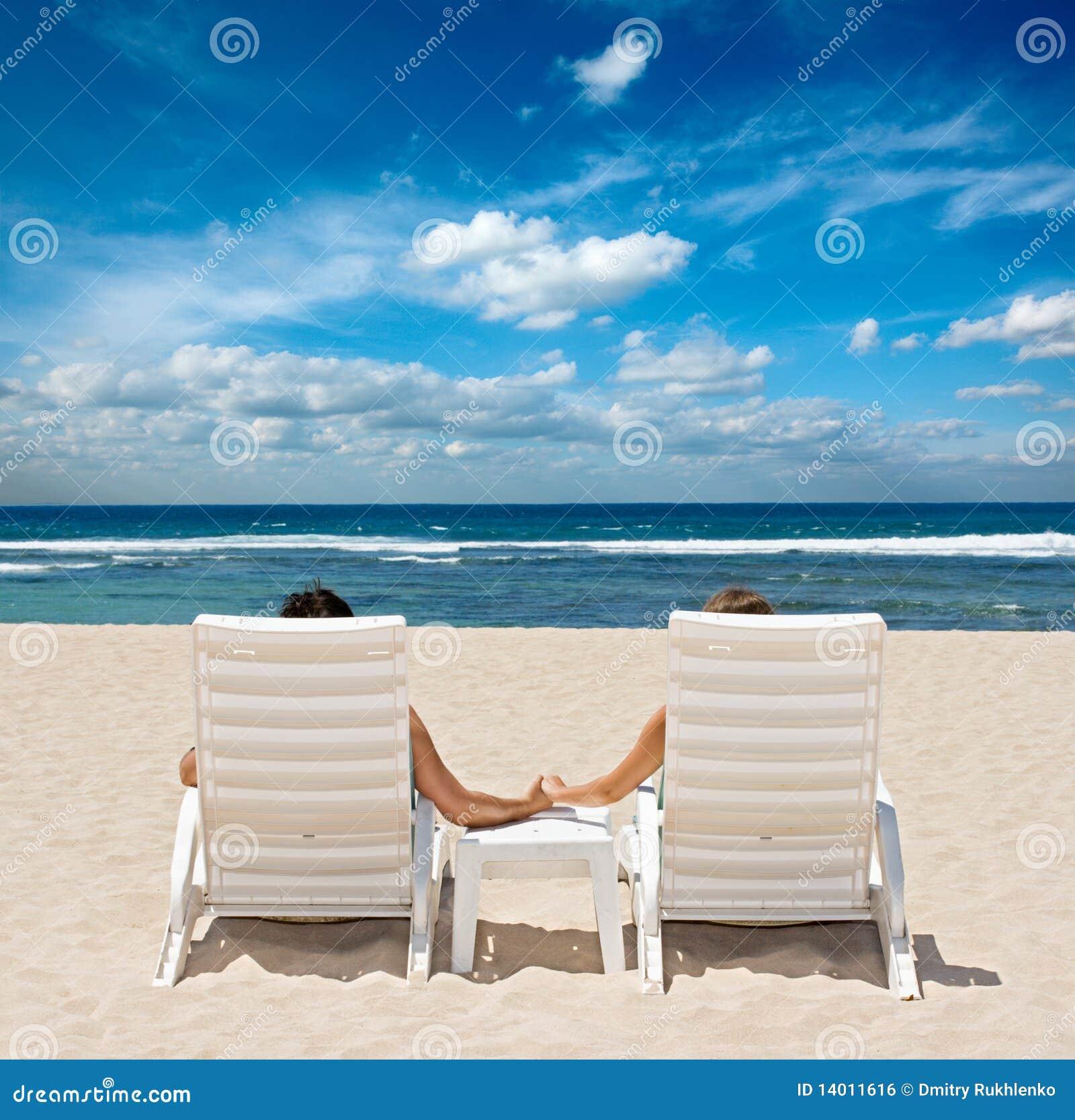 Couples dans des présidences de plage retenant des mains
