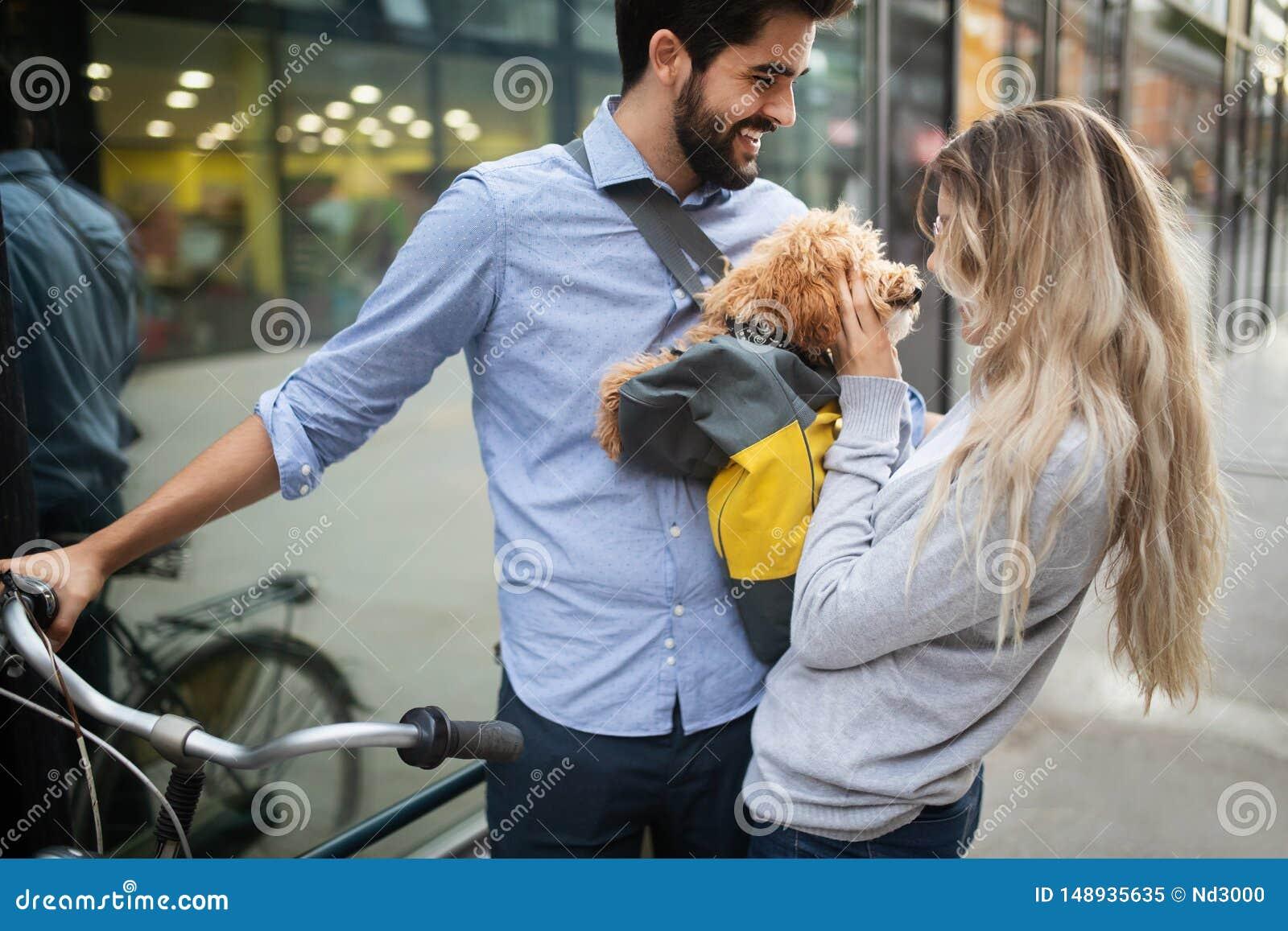 Couples dans l amour avec le chien marchant et souriant ext?rieur