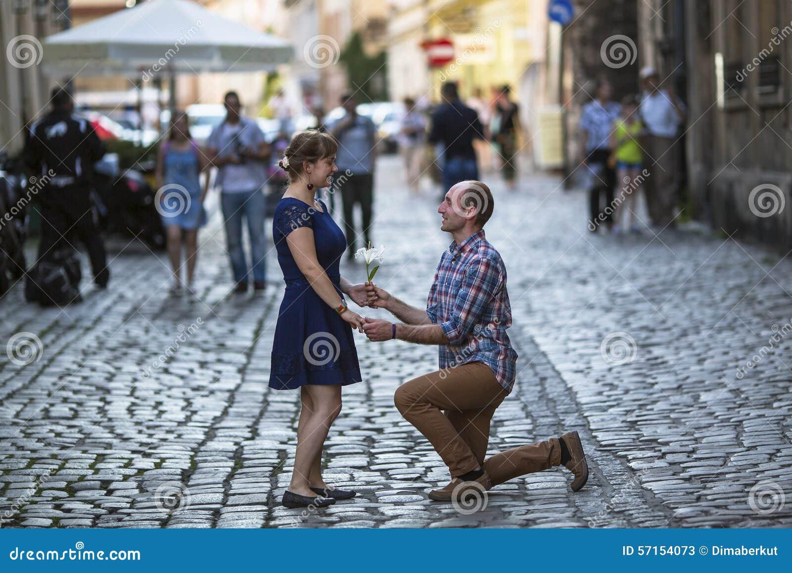couples dans l 39 amour sur la rue l 39 homme sur ses genoux donne une femme une fleur fait une. Black Bedroom Furniture Sets. Home Design Ideas
