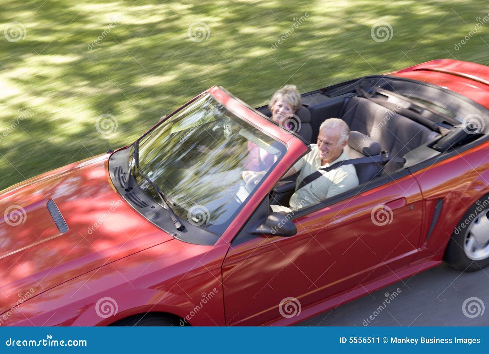 Couples dans le sourire convertible de véhicule