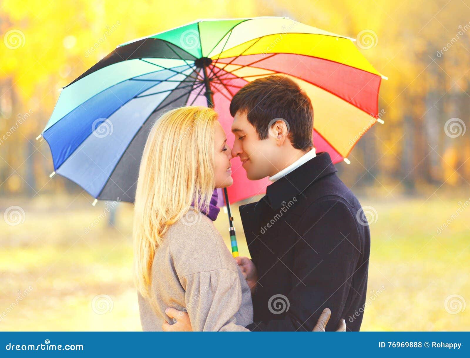 Couples de baiser romantiques de portrait dans l amour avec le parapluie coloré ensemble au jour ensoleillé chaud au-dessus des f