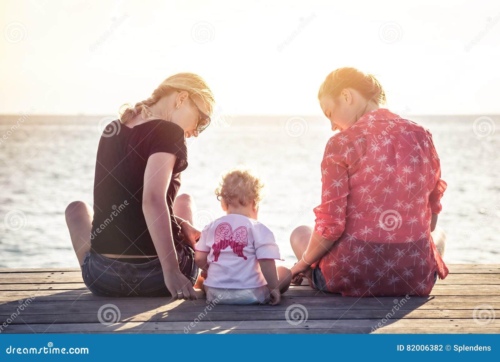 Couples de deux jeunes femmes avec l enfant s asseyant sur la jetée en bois pendant le coucher du soleil avec l horizon au-dessus