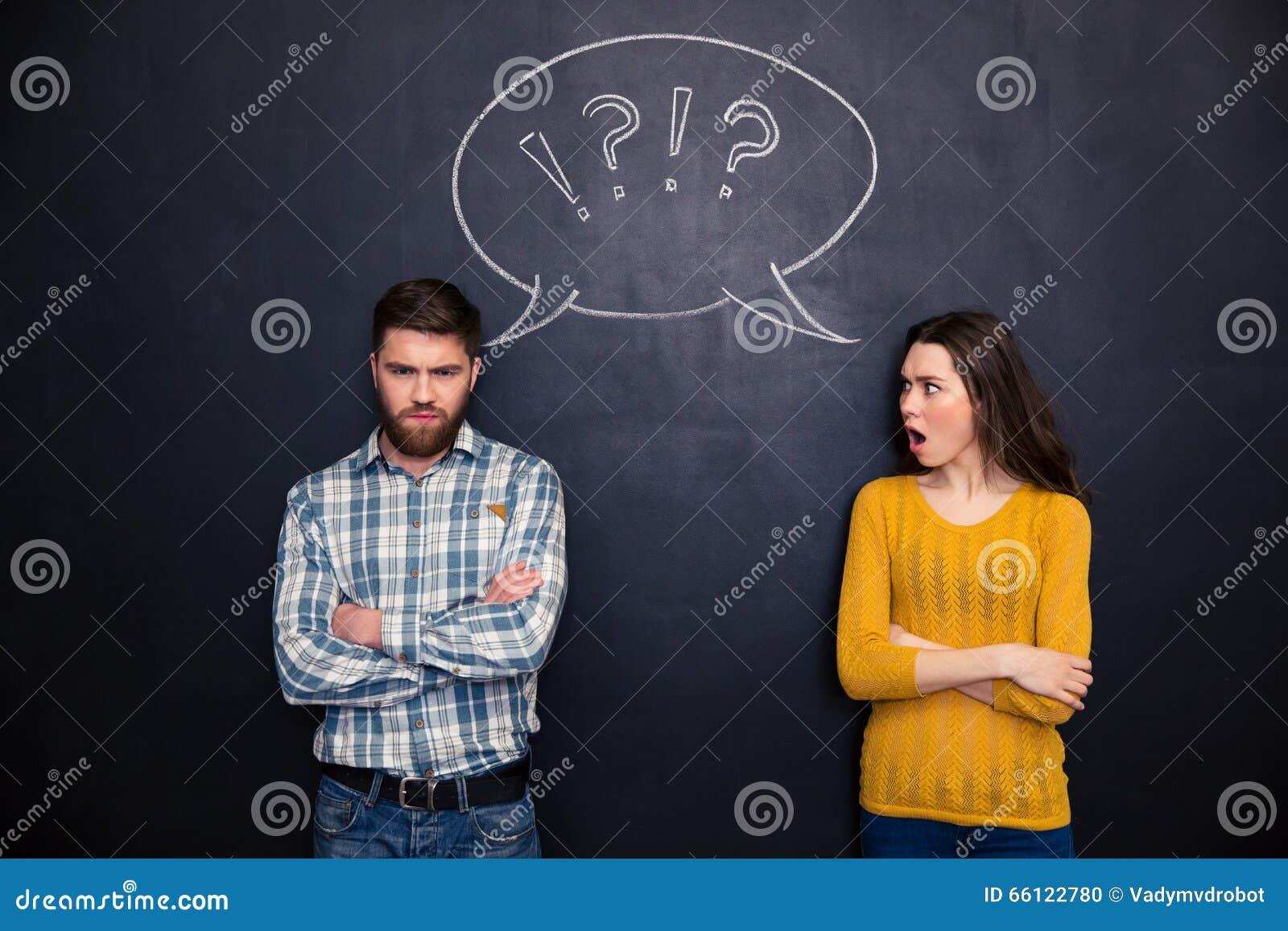 Couples de froncement de sourcils se tenant après argument au-dessus de fond de tableau