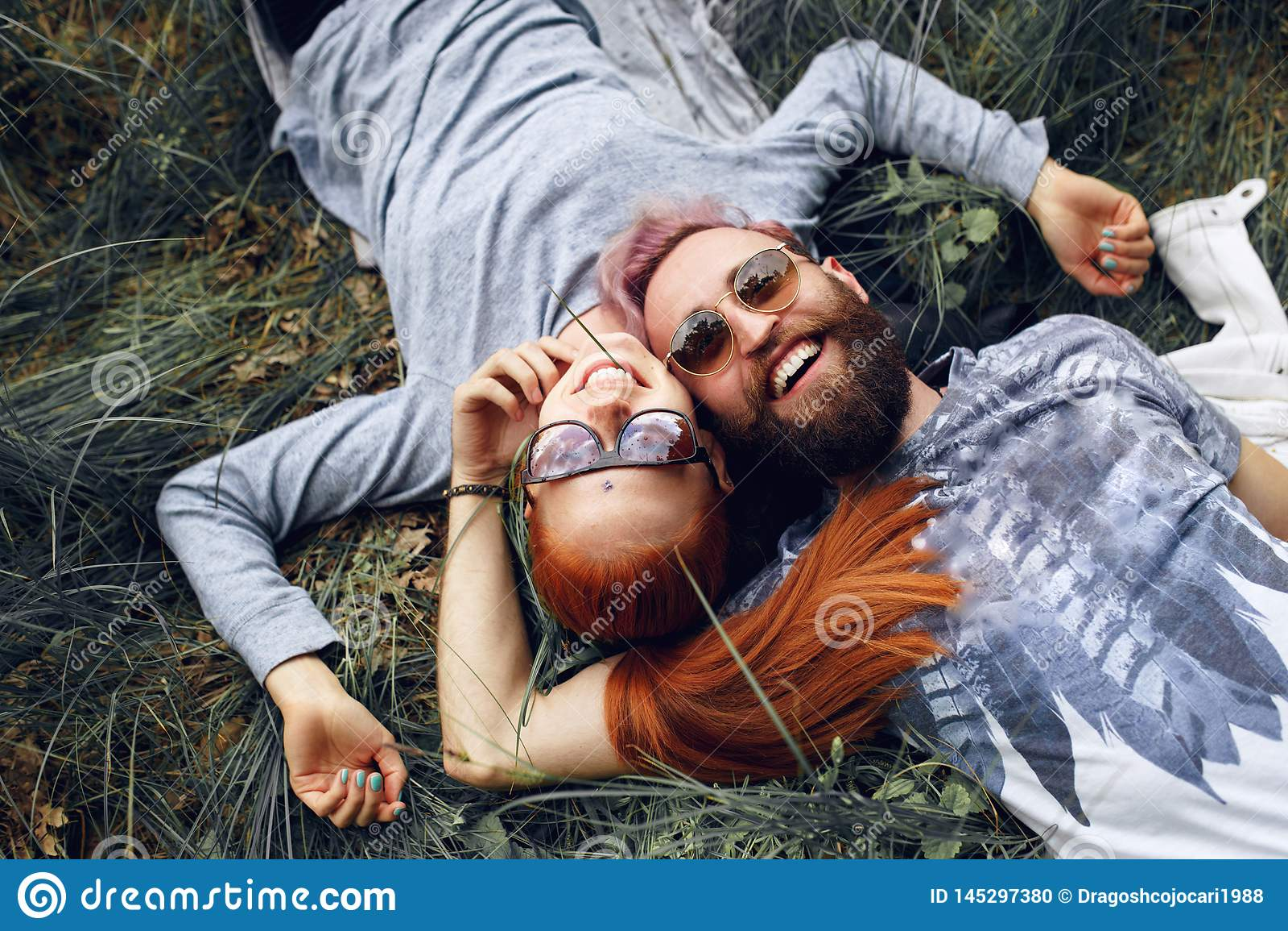 Couples de hippie de bonheur, dans des lunettes de soleil, femme d une chevelure rouge et homme barbu, assis vers le bas sur une