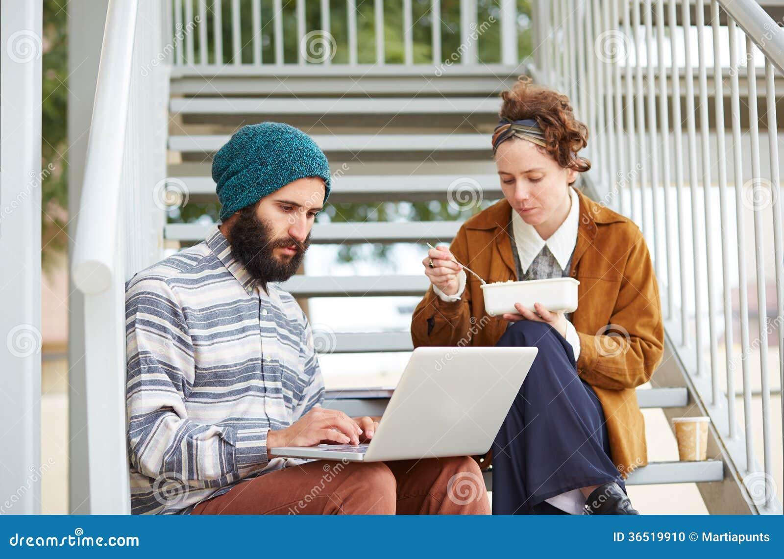 Couples de hippie utilisant l ordinateur et de consommation le déjeuner dehors