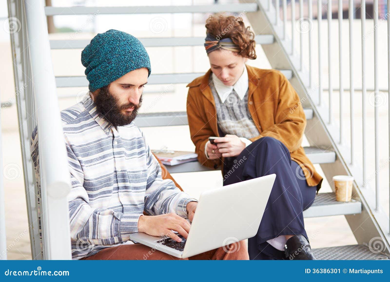 Couples de hippie utilisant l ordinateur et le smartphone dehors
