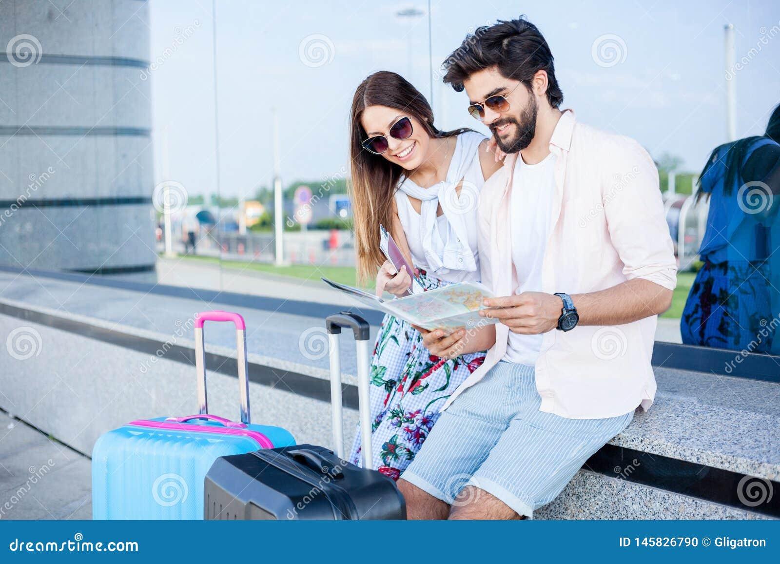 Couples de jeunes touristes s asseyant devant un terminal d aéroport et regardant la carte