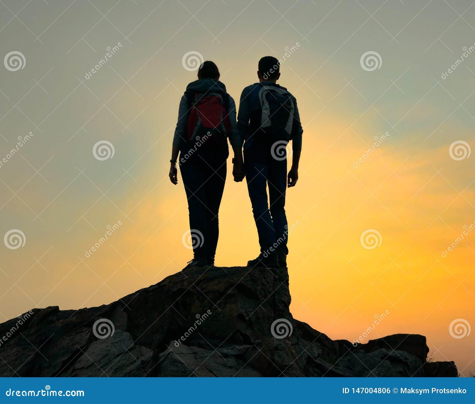 Couples de jeunes voyageurs avec le sac à dos se tenant sur le dessus de la roche au coucher du soleil d été Concept de voyage et