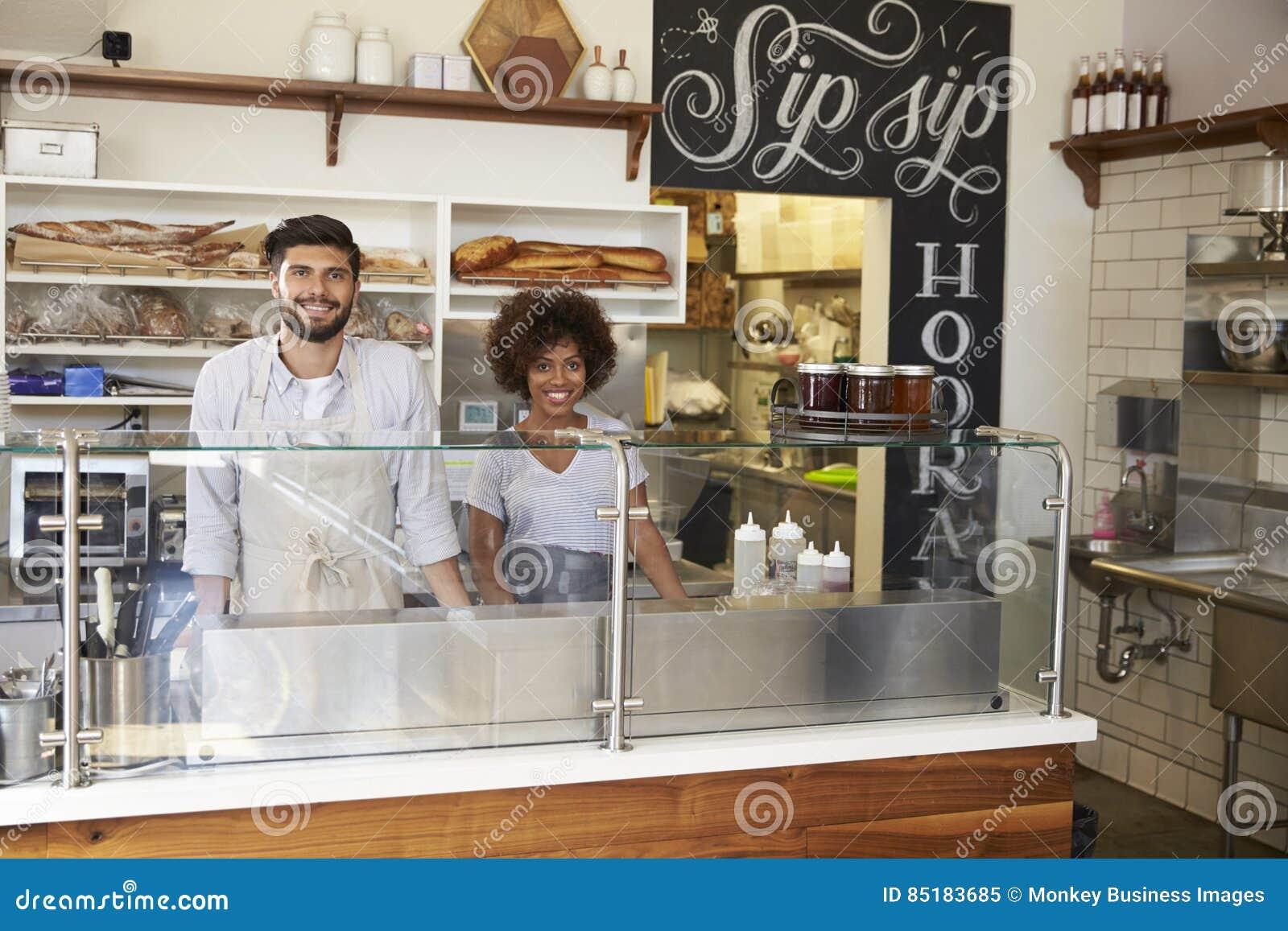 Couples de métis derrière le compteur à une barre de sandwich