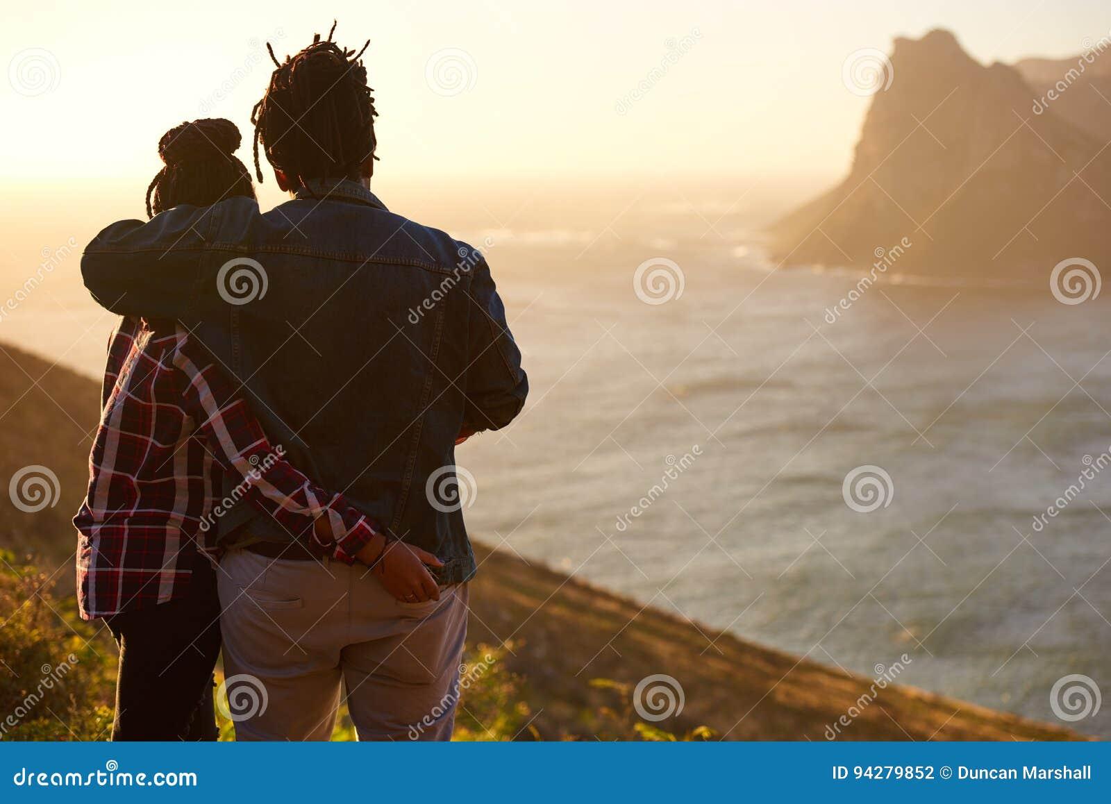 Couples de métis se tenant ensemble observants la vue par derrière