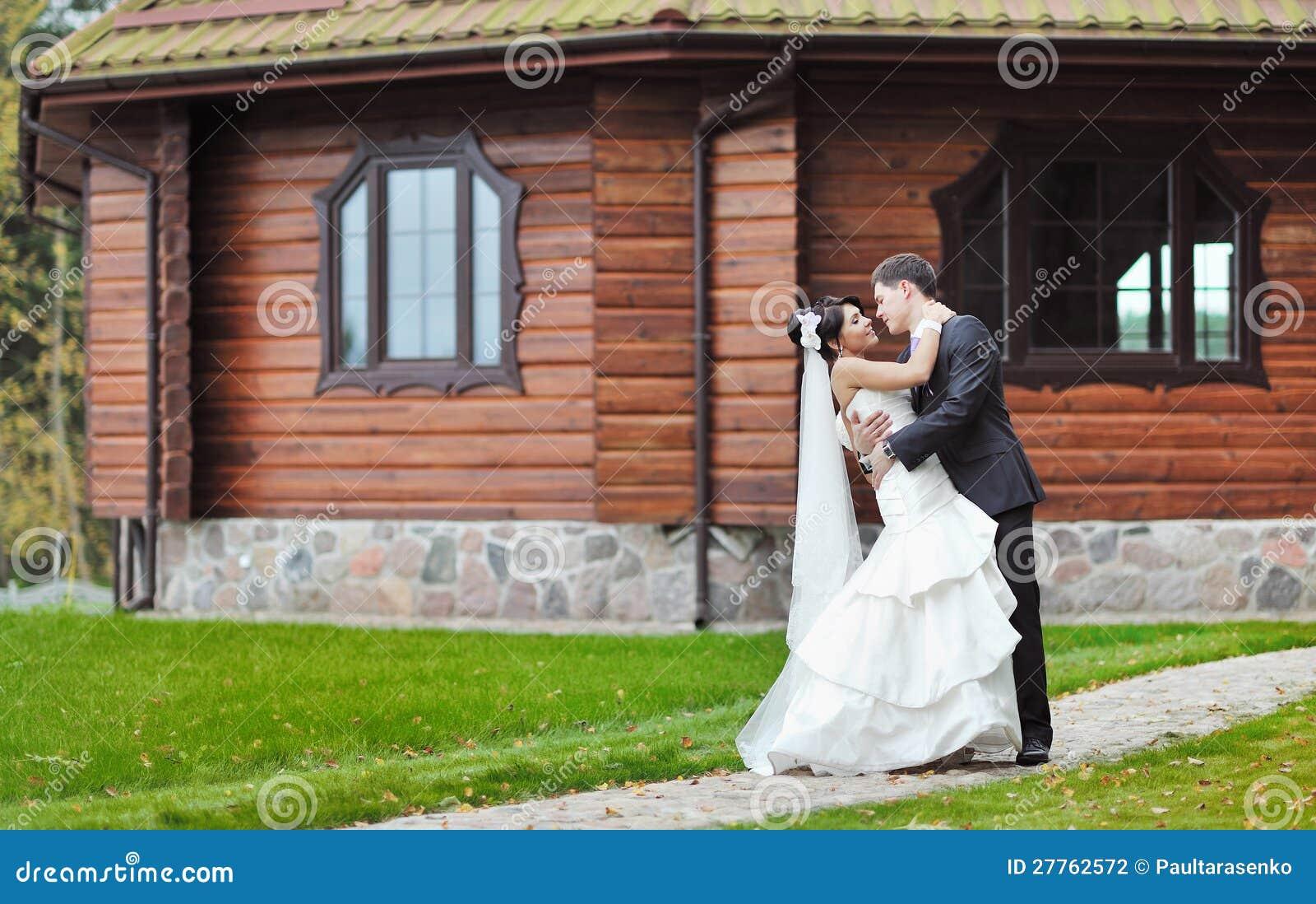 Couples de mariage devant la grande maison en stationnement