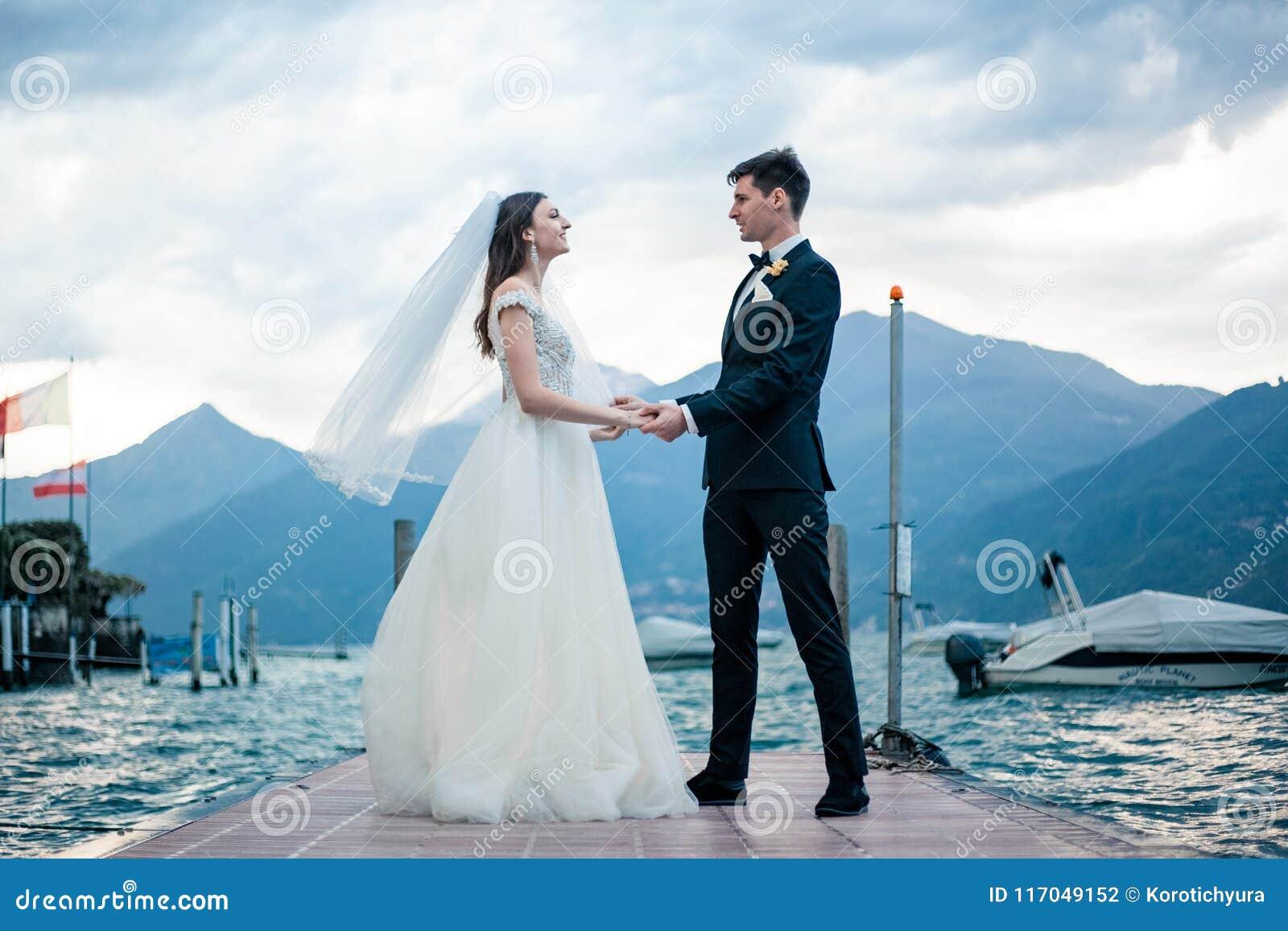 Couples de mariage embrassant sur le fond d un lac et des montagnes