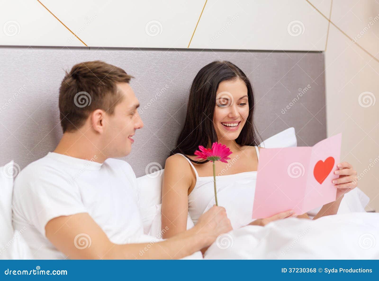 couples de sourire dans le lit avec la carte postale et la fleur photos libres de droits image. Black Bedroom Furniture Sets. Home Design Ideas