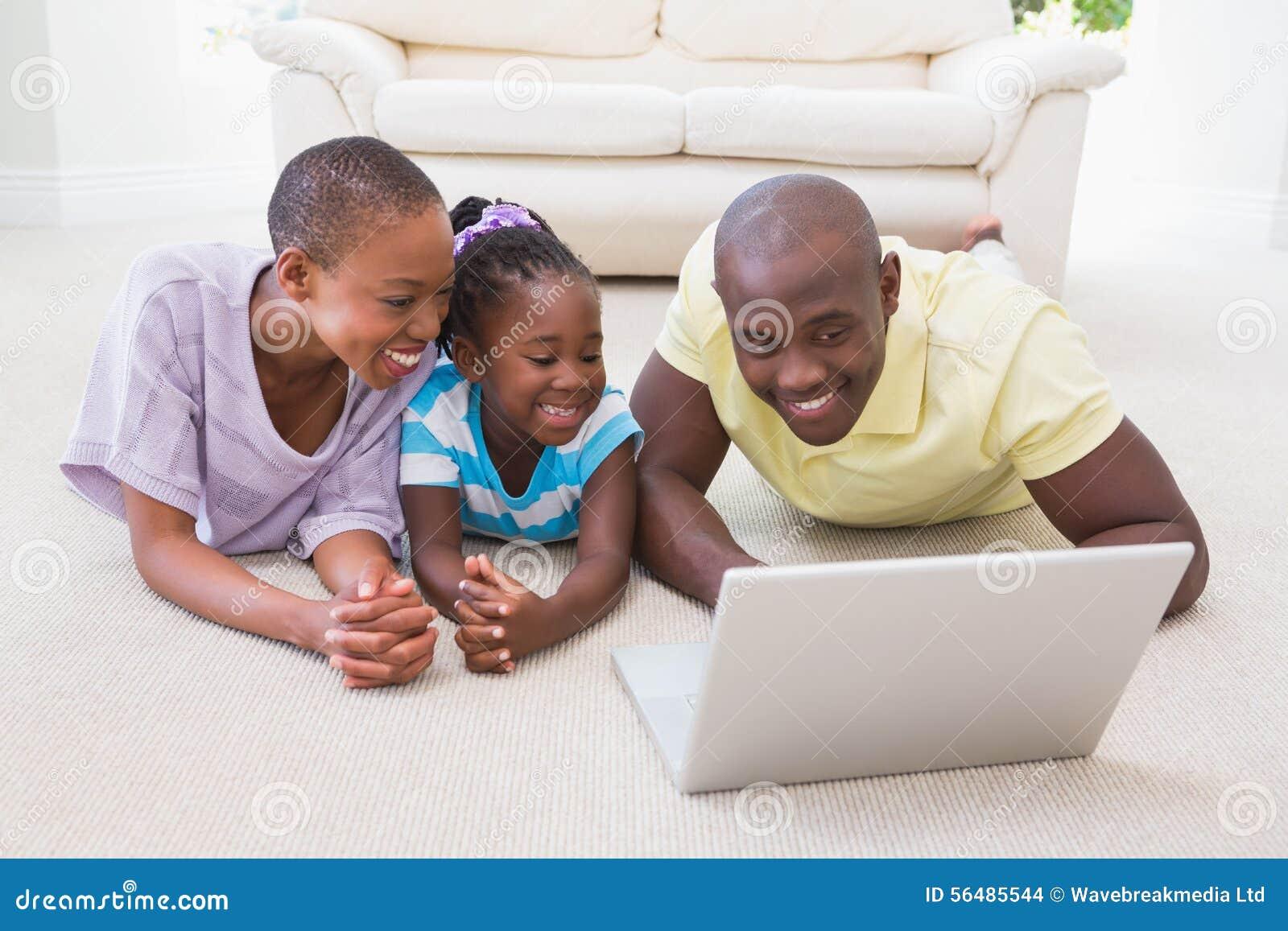 Couples de sourire heureux utilisant l ordinateur portable avec leur fille