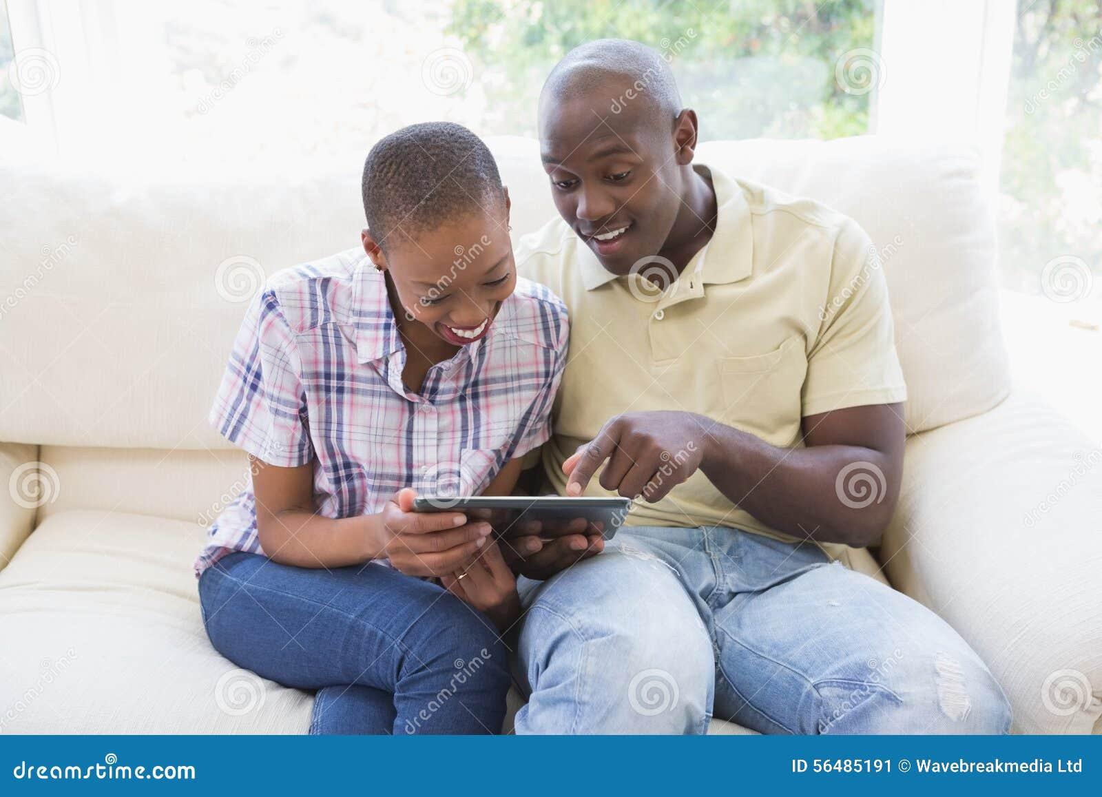 Couples de sourire heureux utilisant le comprimé numérique