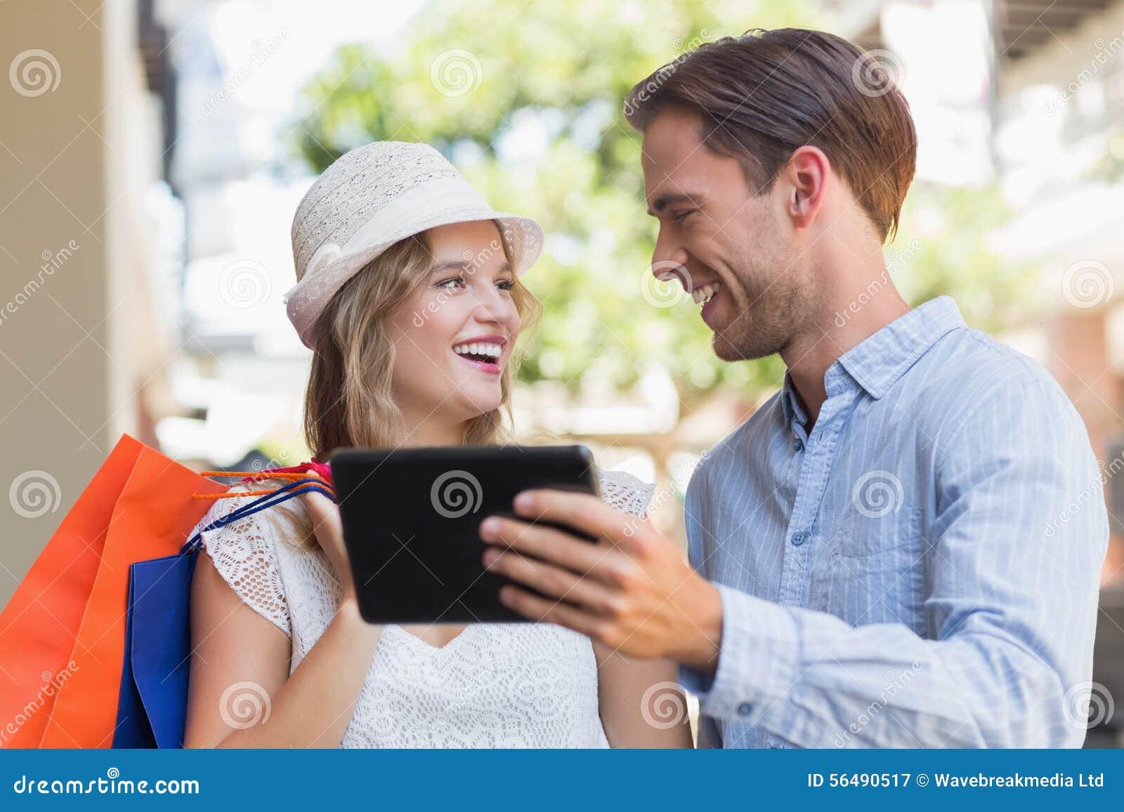 Couples de sourire mignons regardant un comprimé