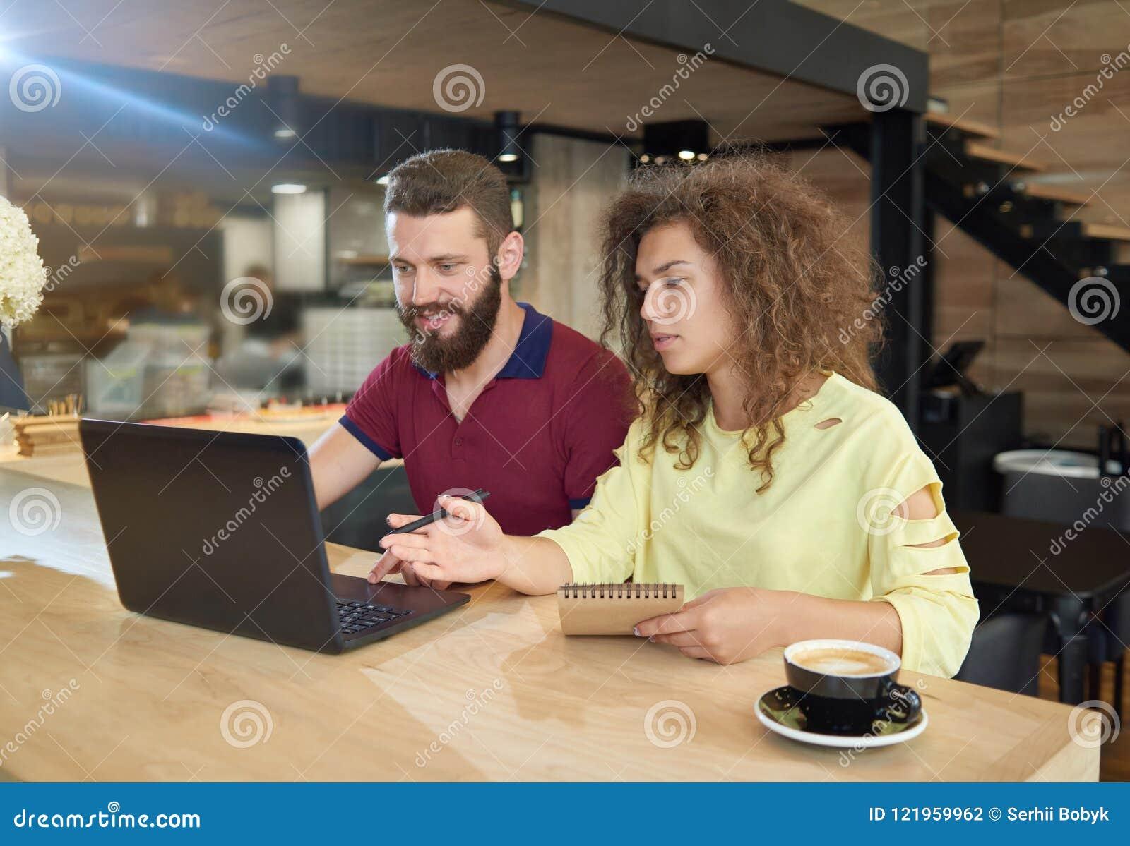 Couples des étudiants étudiant en café utilisant l ordinateur portable