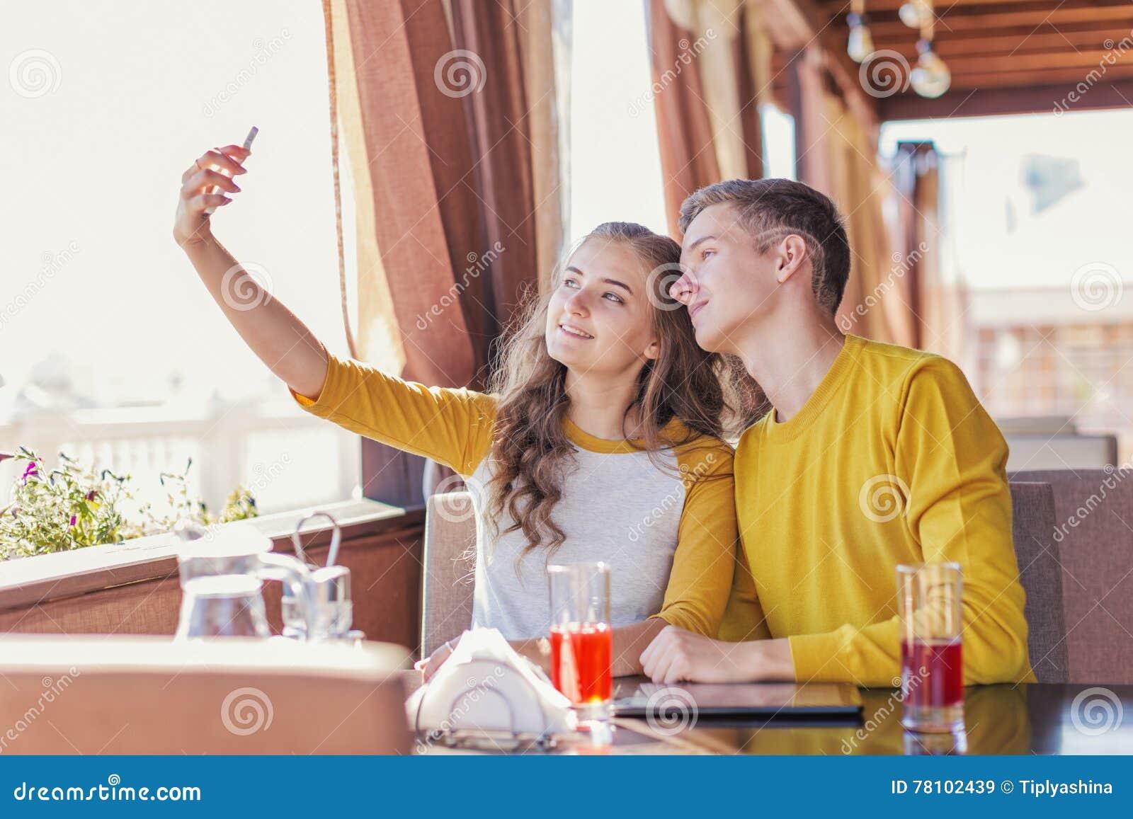 Couples des adolescents dans un café d été