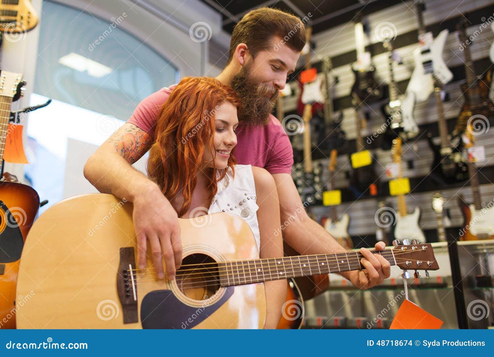 couples des musiciens avec la guitare au magasin de guitar vectors