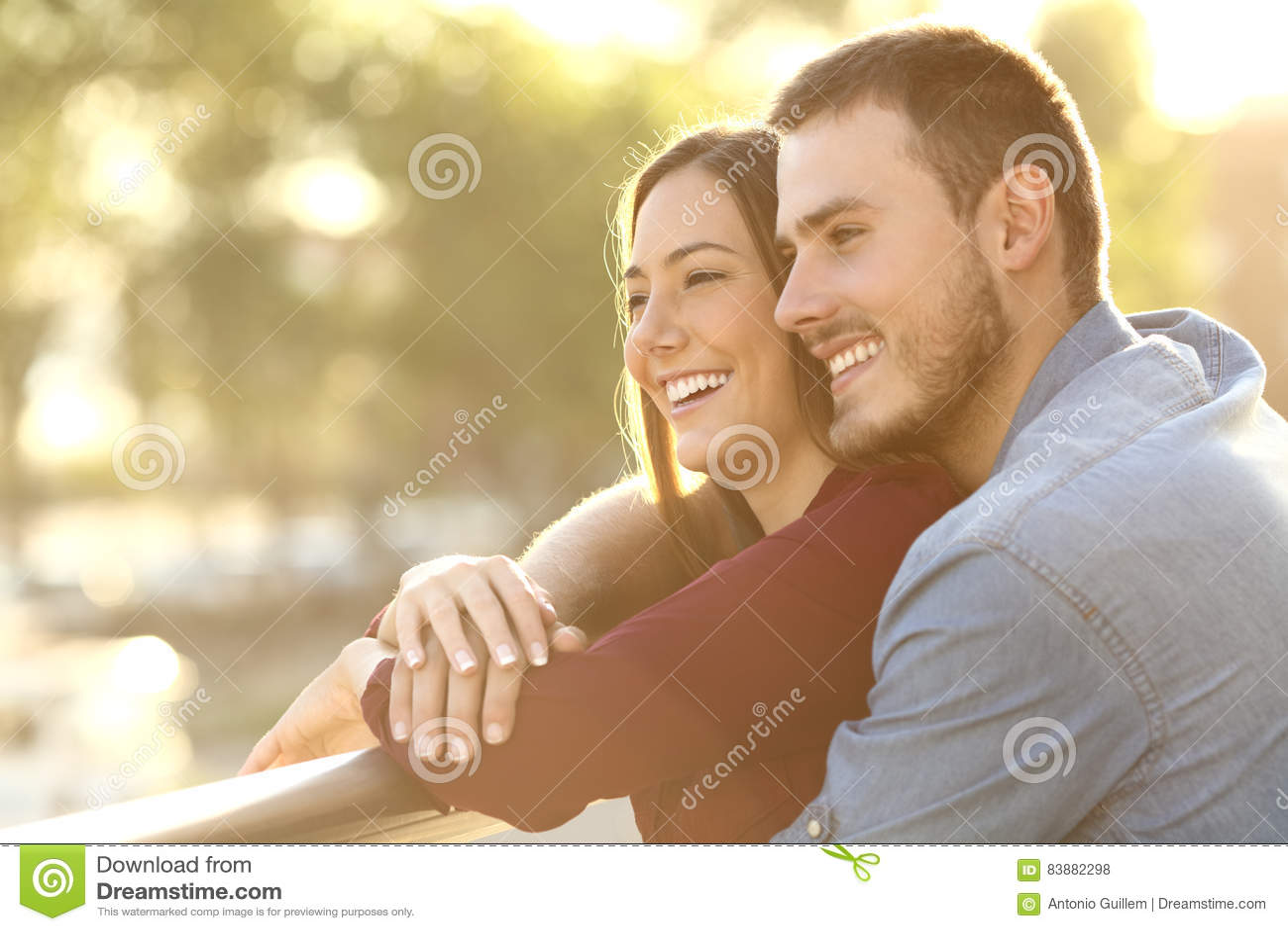 Couples embrassant au coucher du soleil dans un balcon