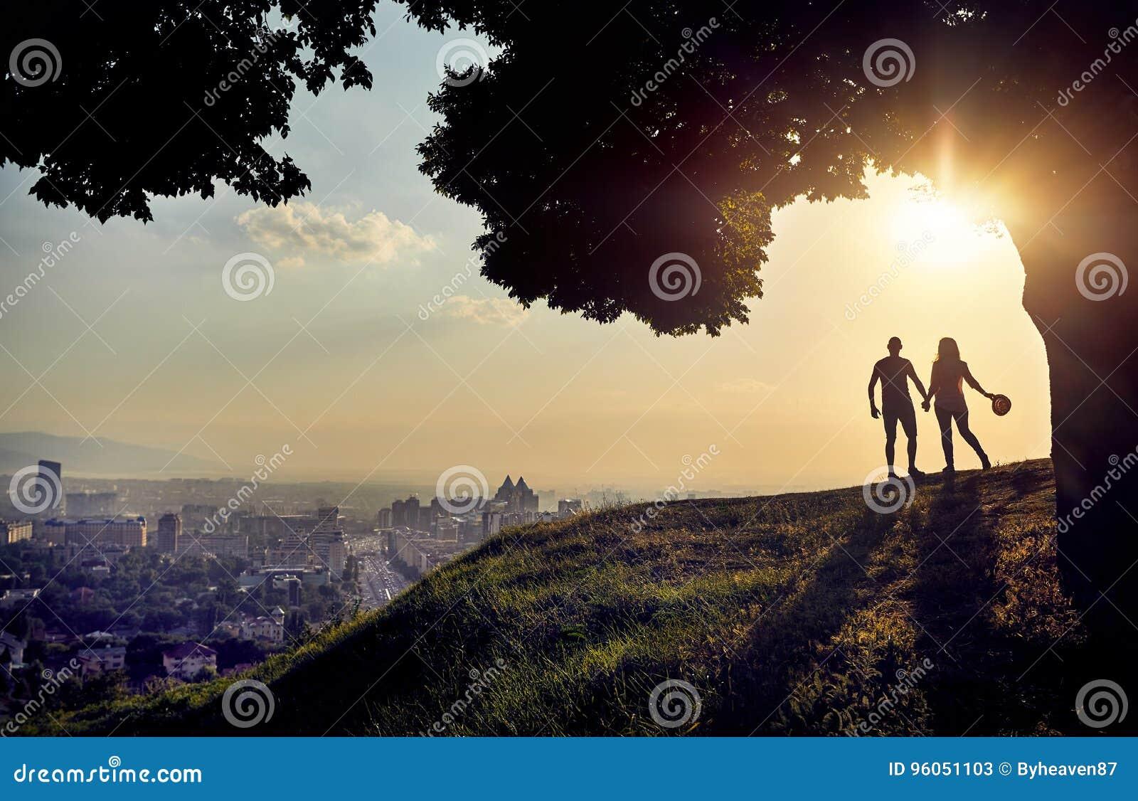 Couples en silhouette à la vue de ville de coucher du soleil