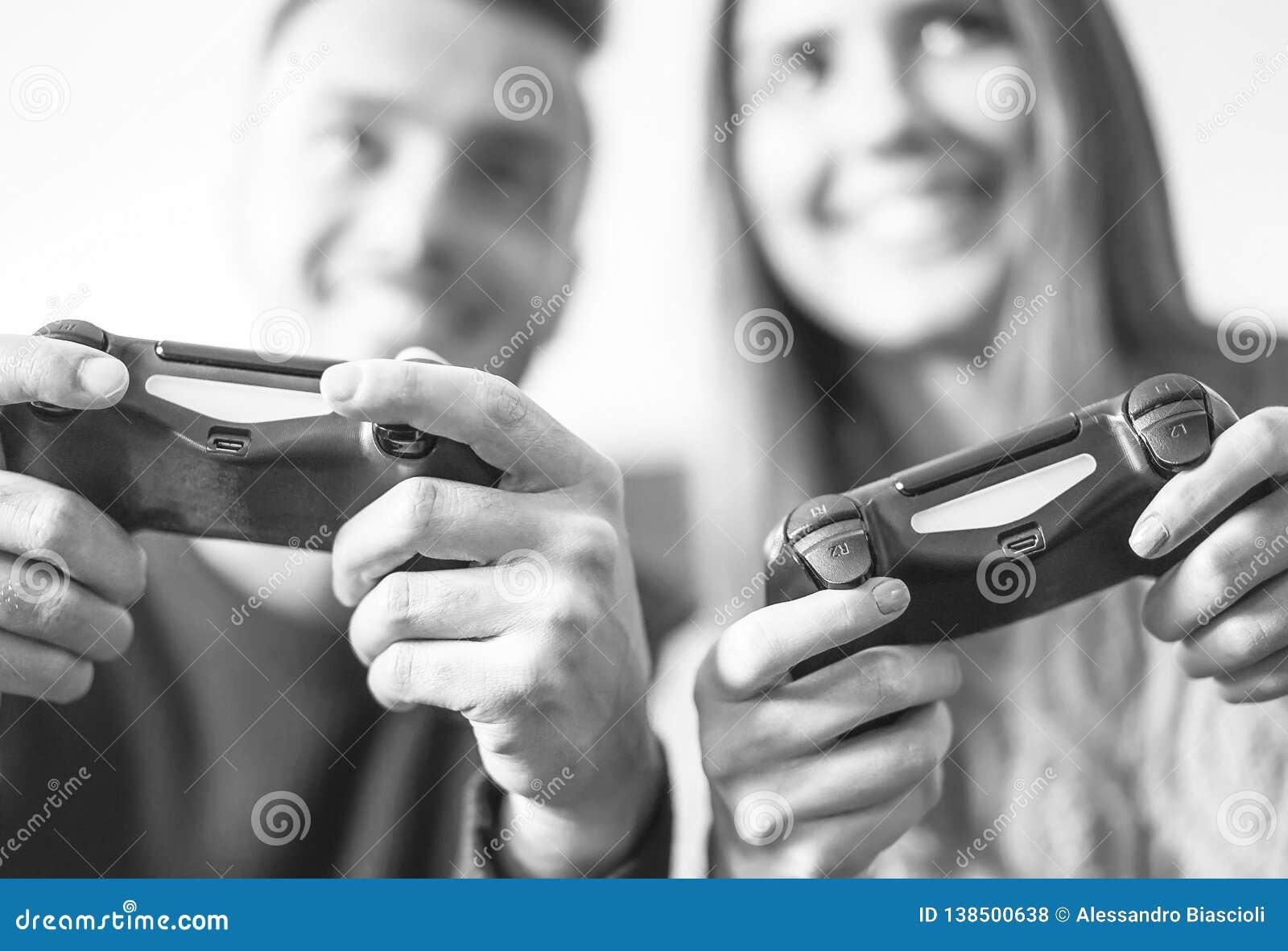 Couples enthousiastes jouant les jeunes heureux de jeux vidéo à la maison - ayant l amusement avec de nouvelles technologies en l