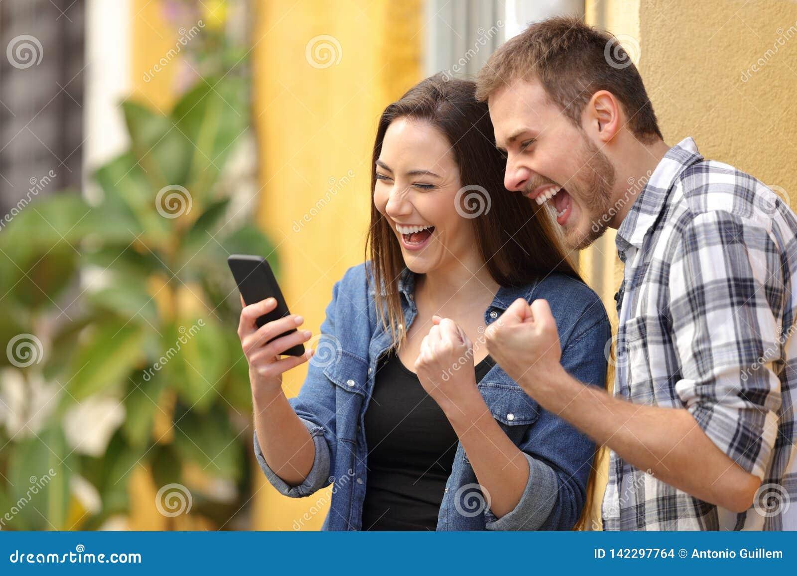 Couples enthousiastes trouvant des offres en ligne au téléphone dans la rue