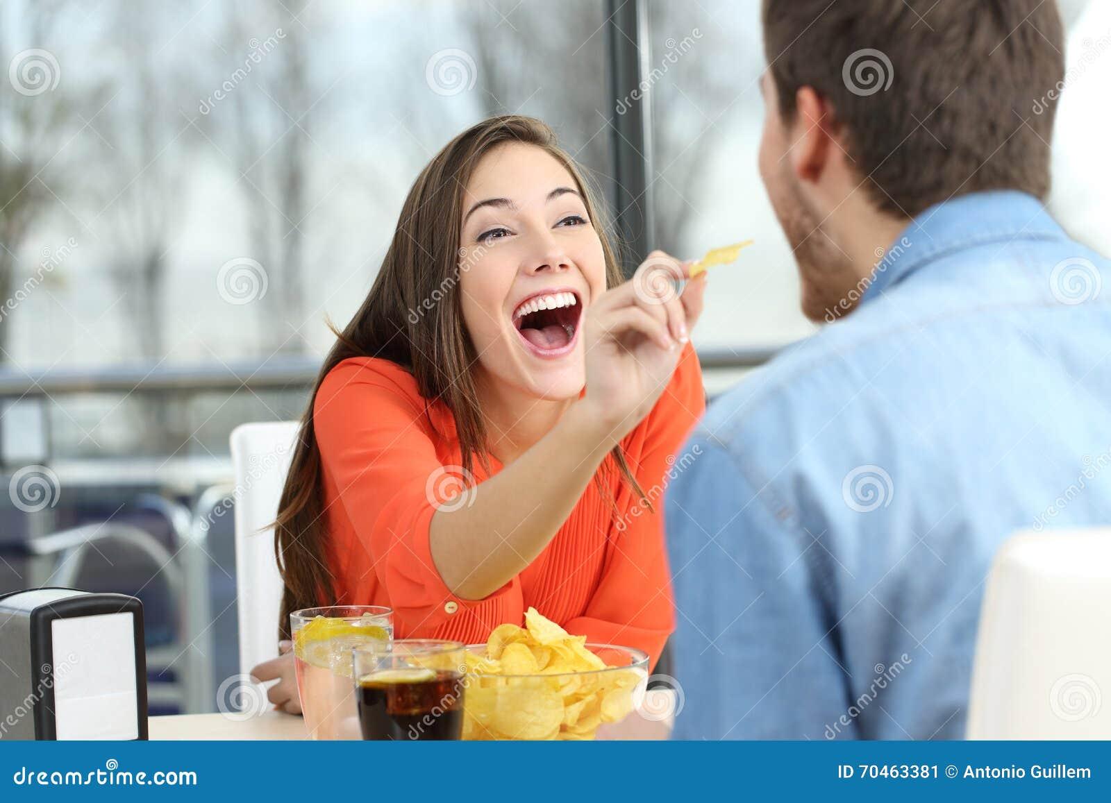 Couples espiègles mangeant des pommes de terre de frite