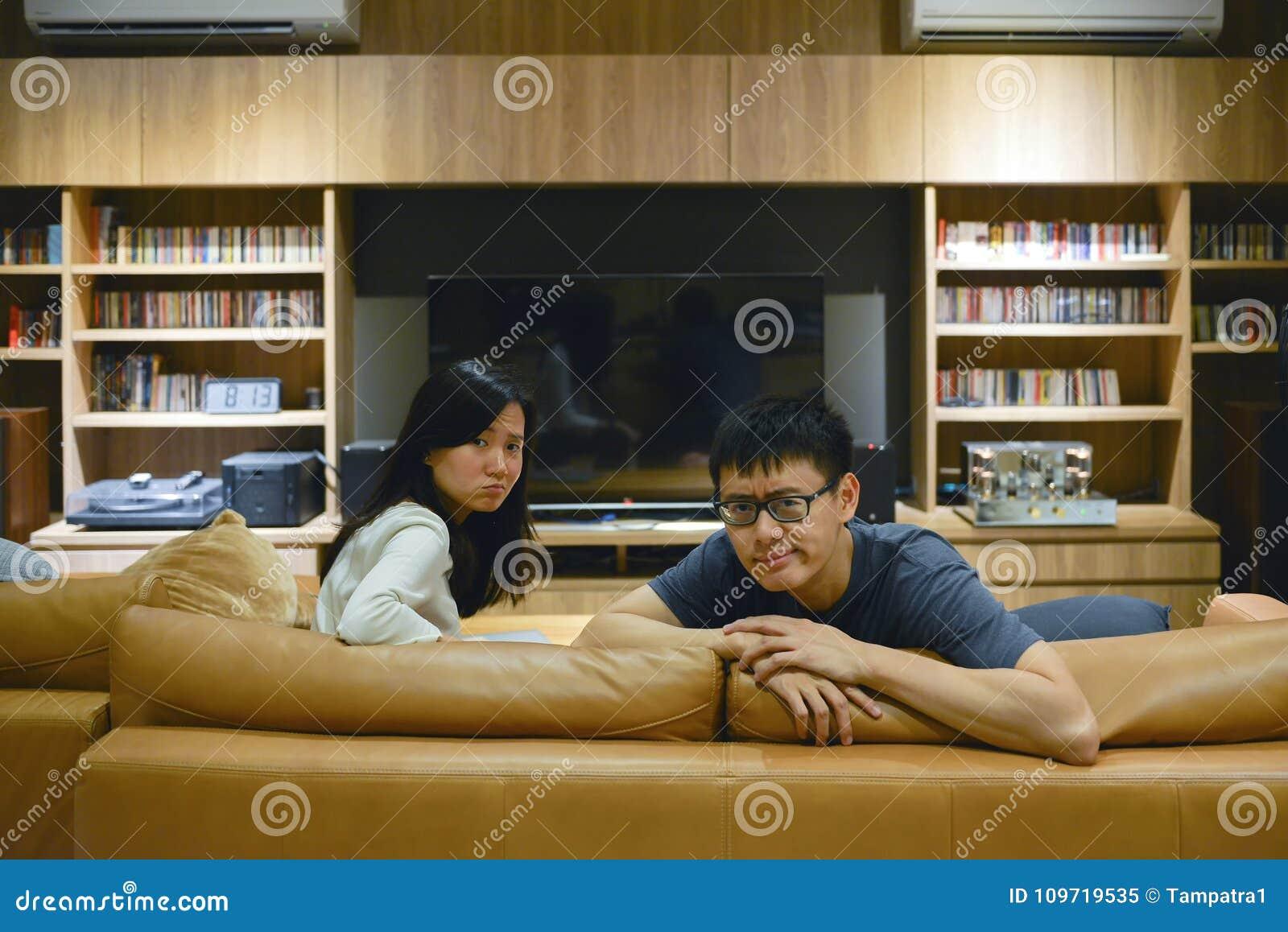 Couples fâchés devant la TV dans le salon la nuit