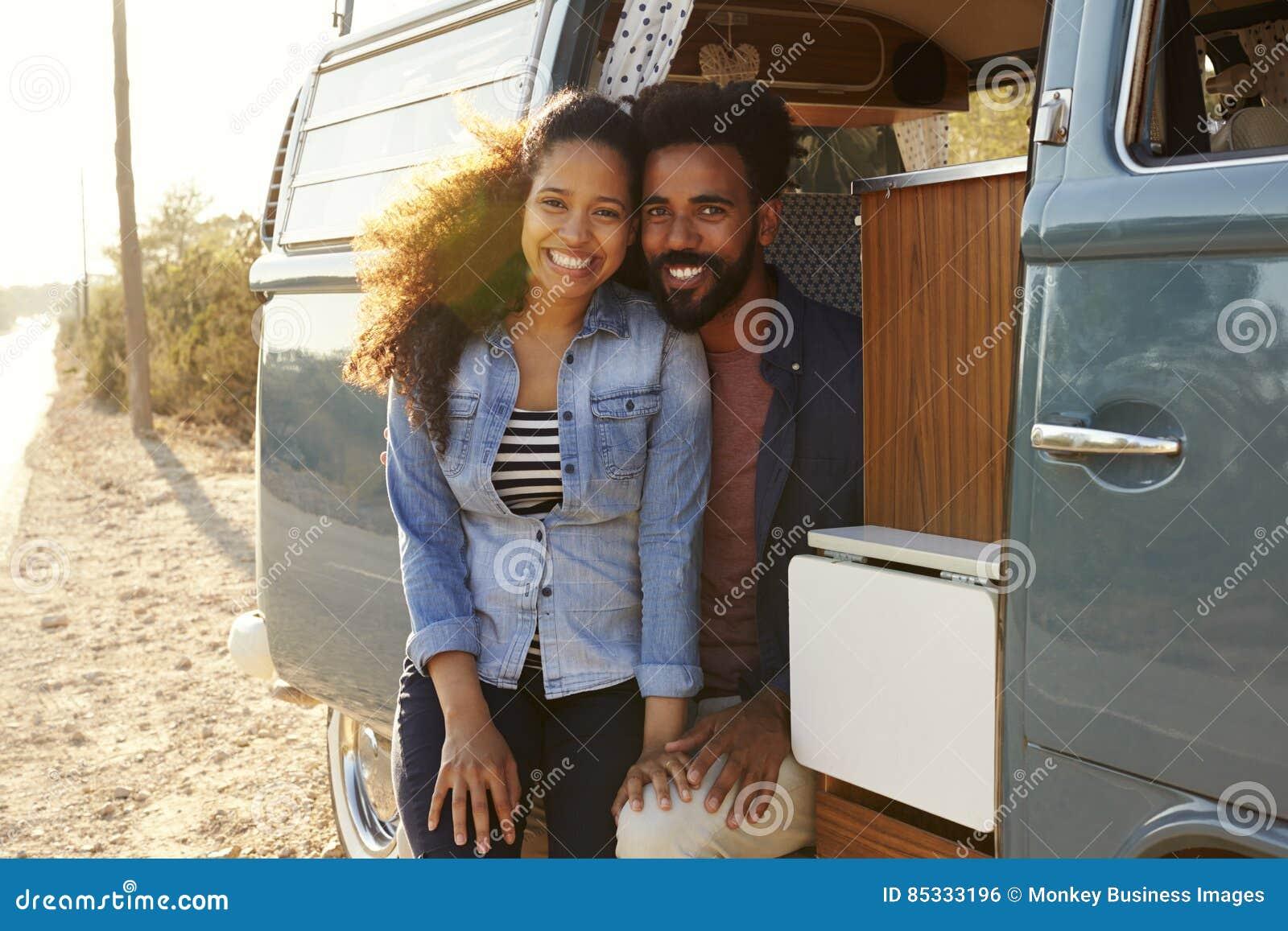 Couples faisant un bord de la route s arrêter dans leur regard de fourgon à l appareil-photo