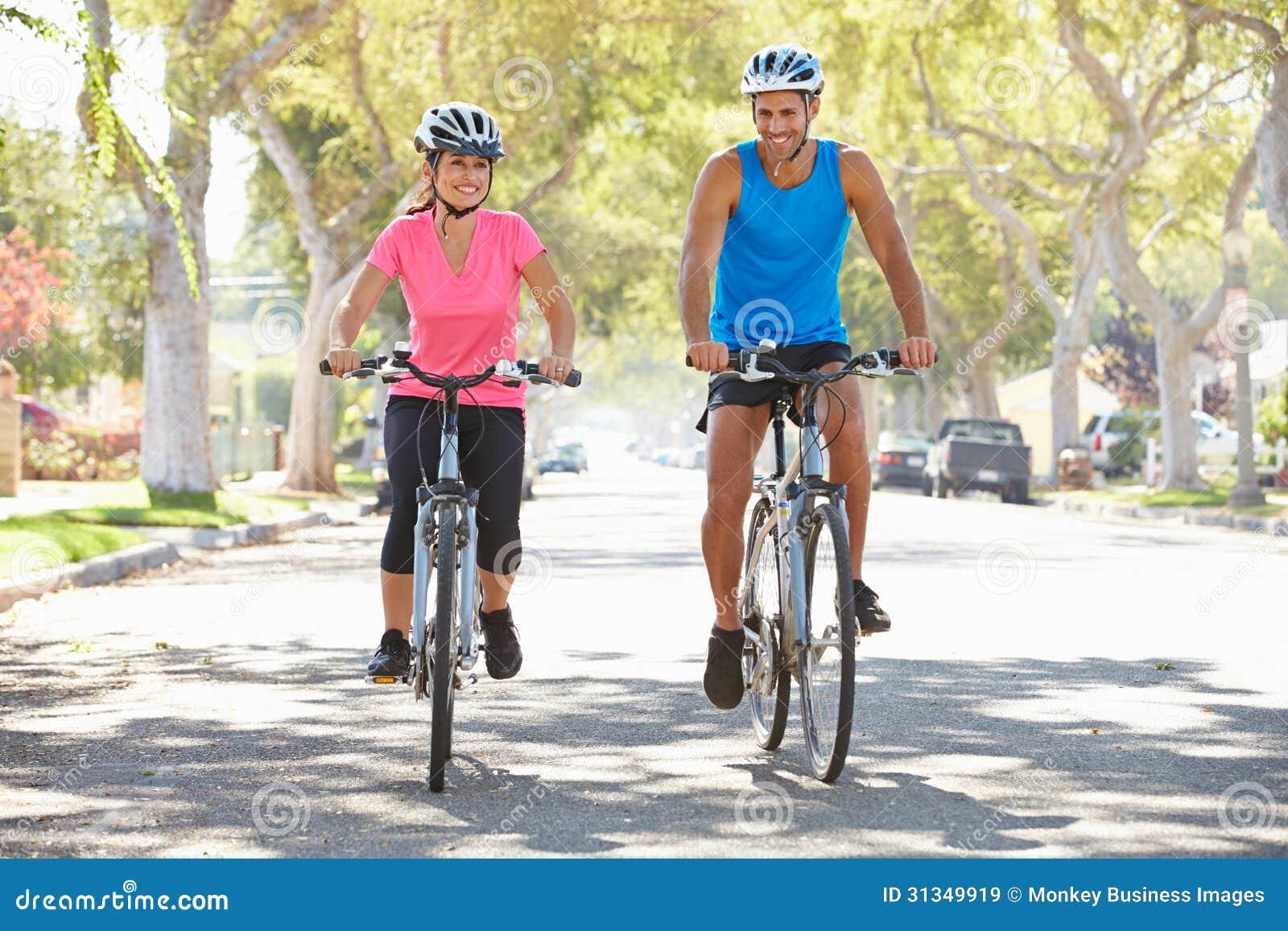 Couples faisant un cycle sur la rue suburbaine