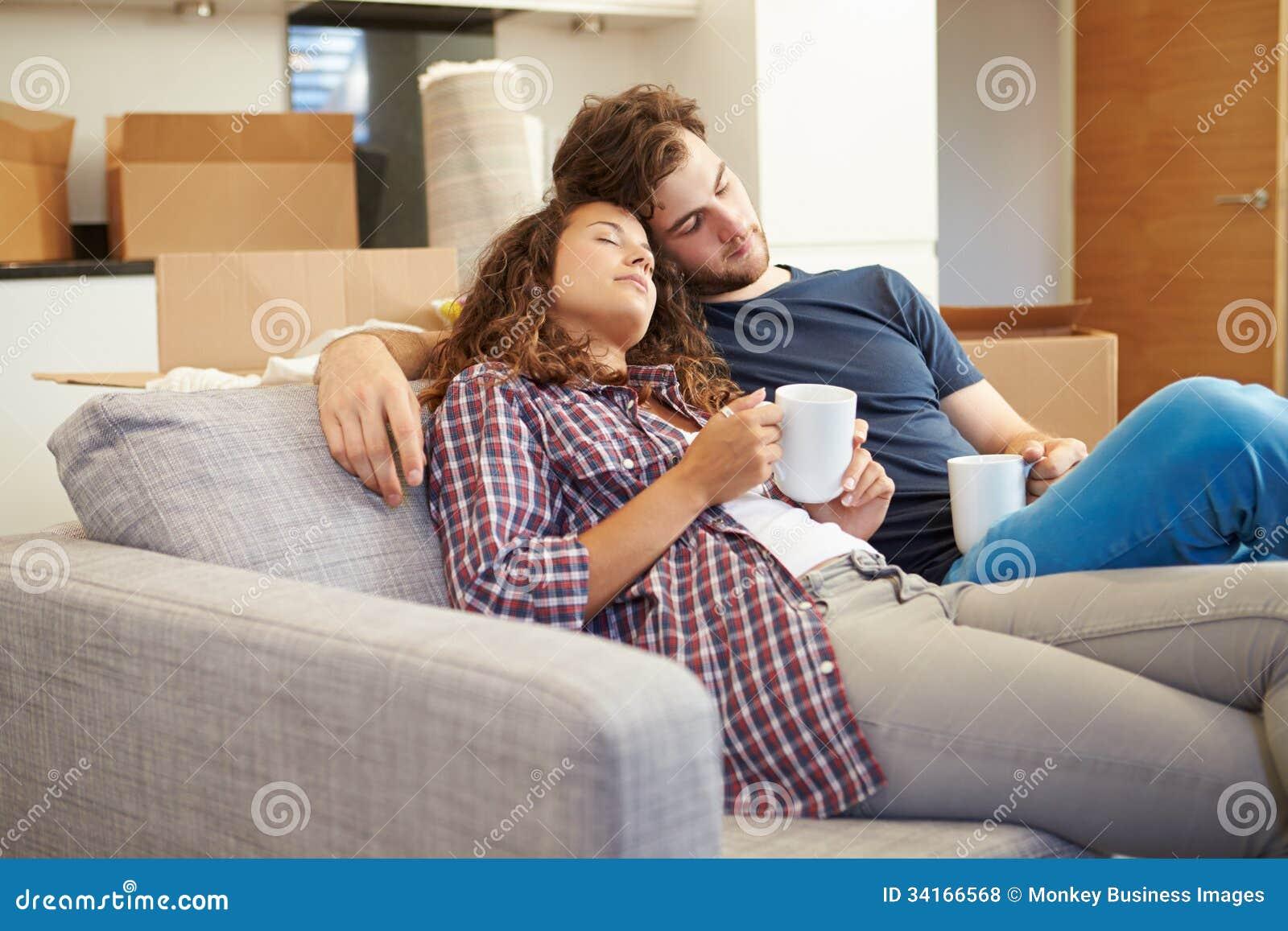 Couples fatigués détendant sur Sofa In New Home