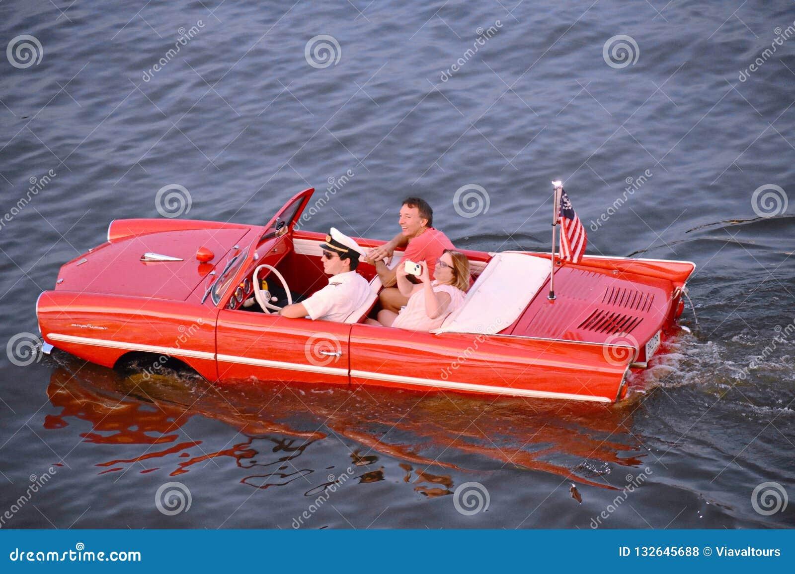 Couples gentils appréciant le tour rouge amphibie de voiture au-dessus du lac bleu à la région de Buena Vista de lac